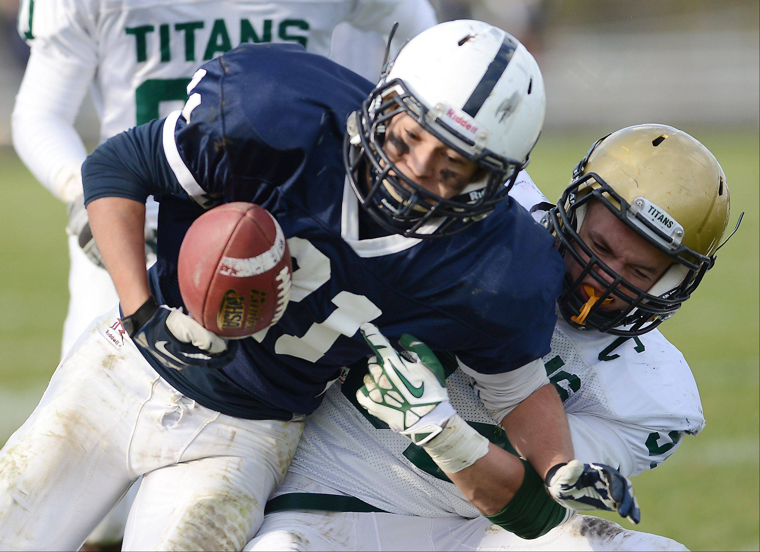 Cary-Grove's Zach McQuade (21) has the ball stripped by Boylan Catholic's Graham Smolirski (32) during Saturday's game in Cary.