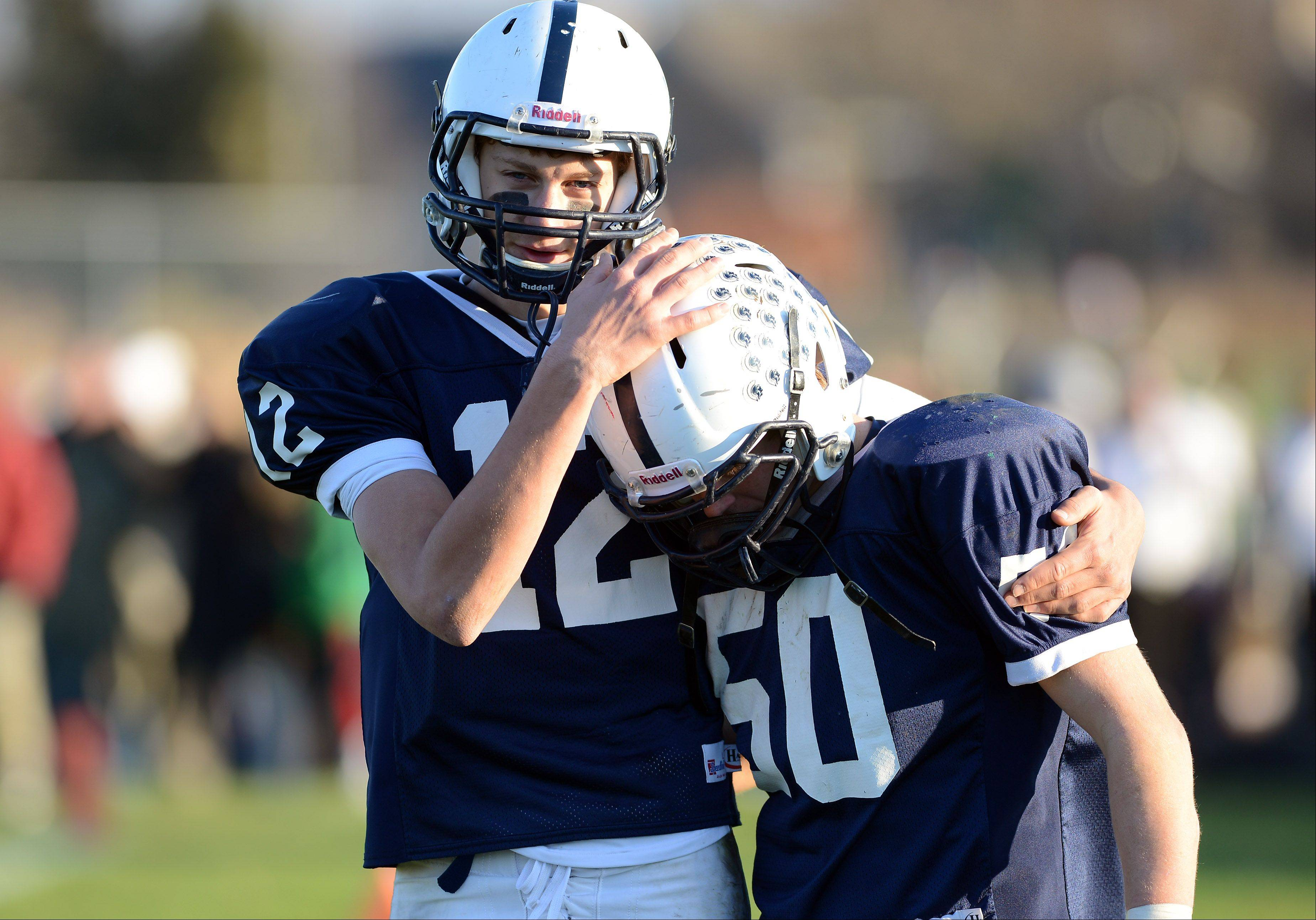 Cary-Grove's Jason Gregoire (12) consoles teammate Emerson Kersten (50) after their loss to Boylan Catholic Saturday in Cary.