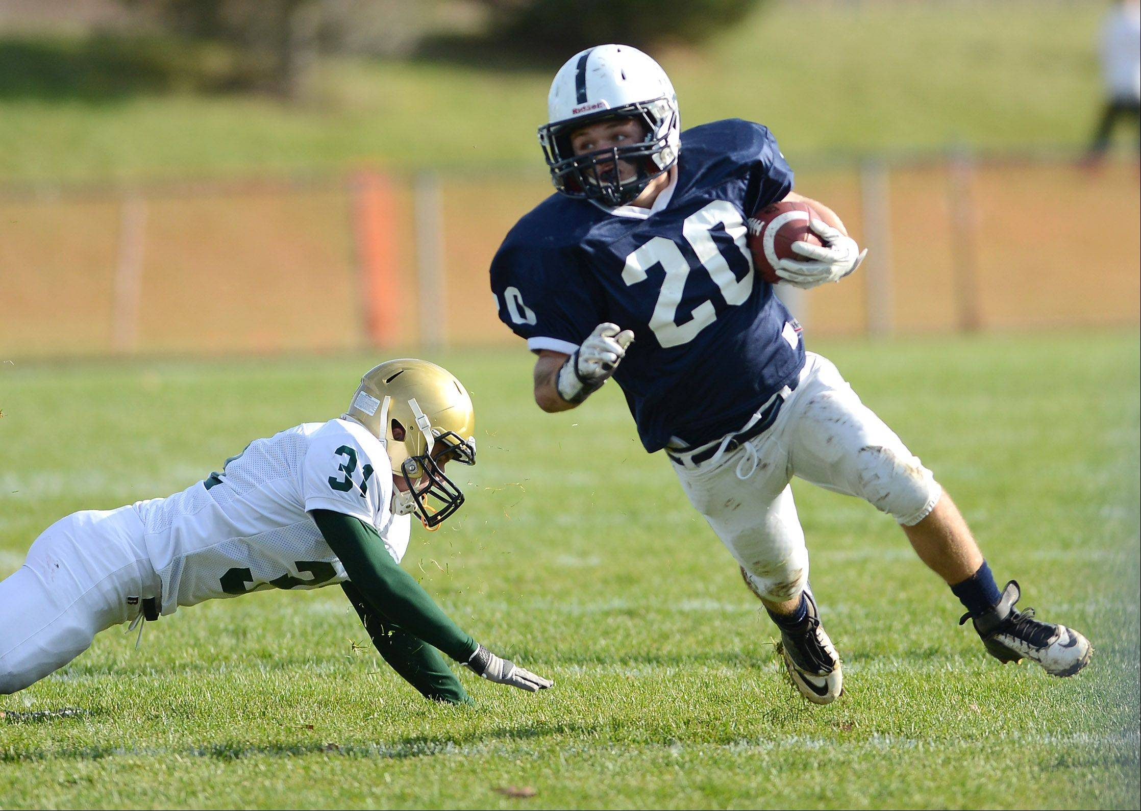 Cary-Grove's Matt Sutherland (20) breaks a run to the outside getting around Boylan Catholic's Steven Hewett (31) during Saturday's game in Cary.