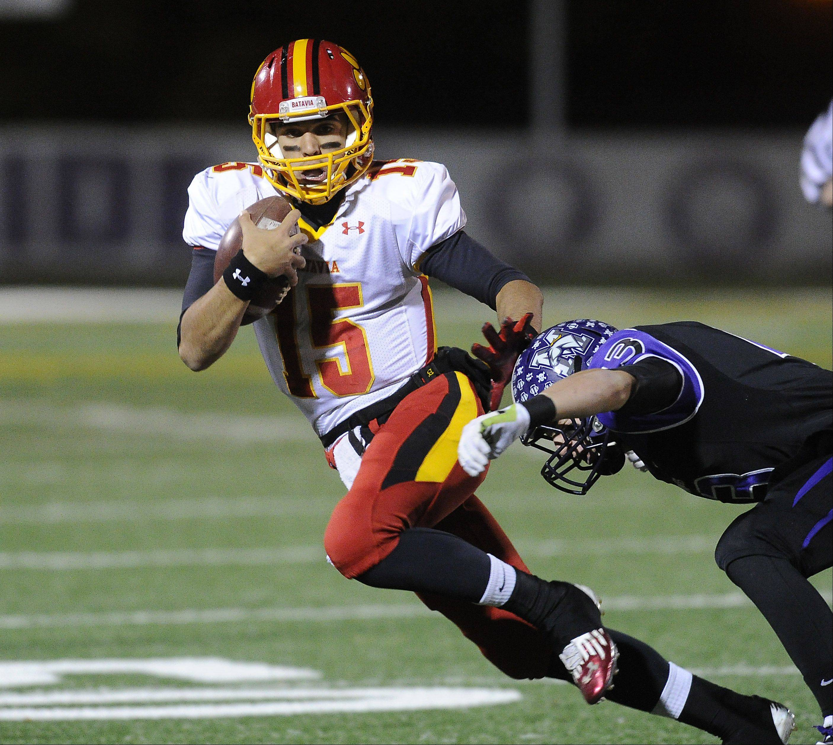 Batavia quarterback Micah Coffey scrambles for yardage in the first quarter as Rolling Meadows' Peyton Dezonna tries for the tackle.
