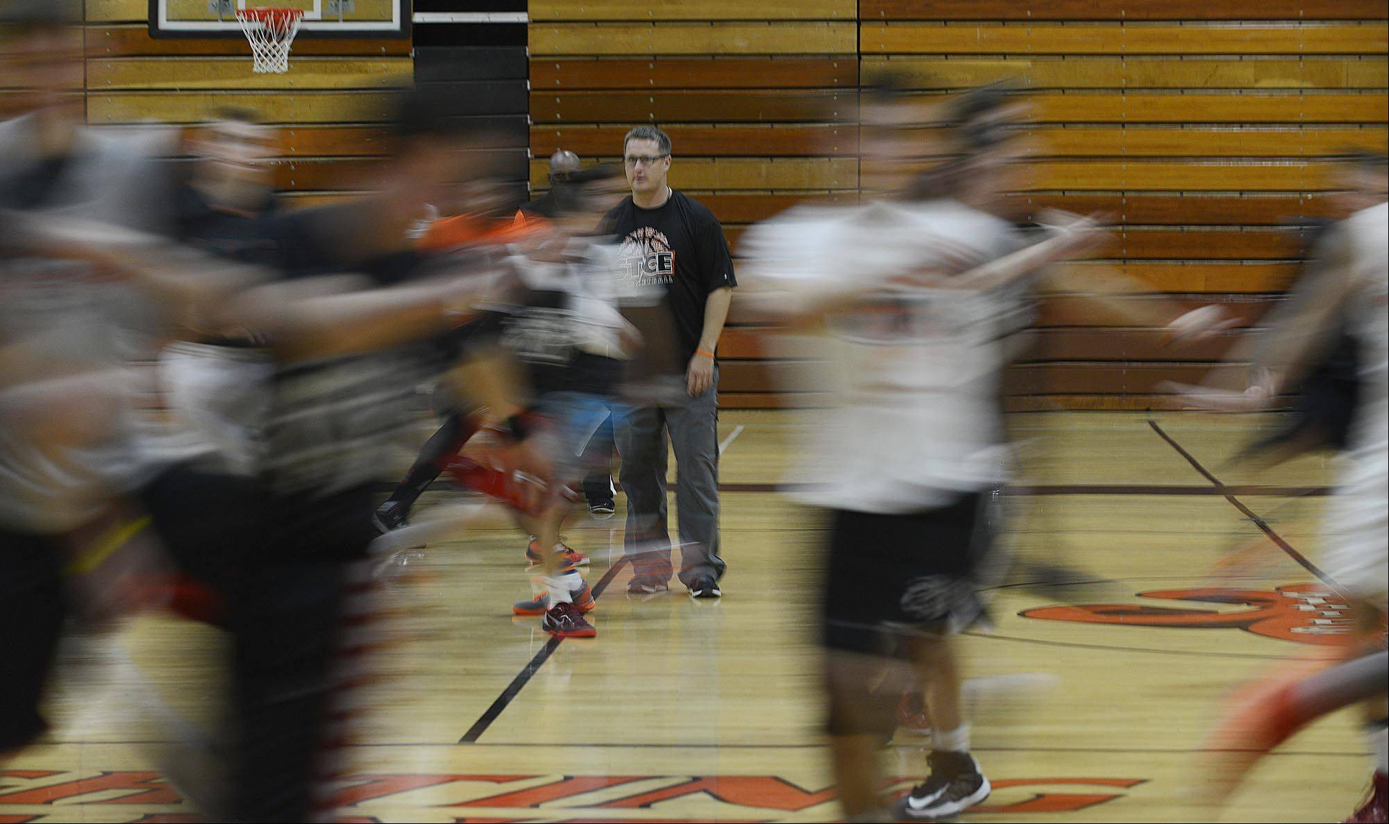 St. Charles East boys basketball coach Pat Woods watches players during tryouts Monday.