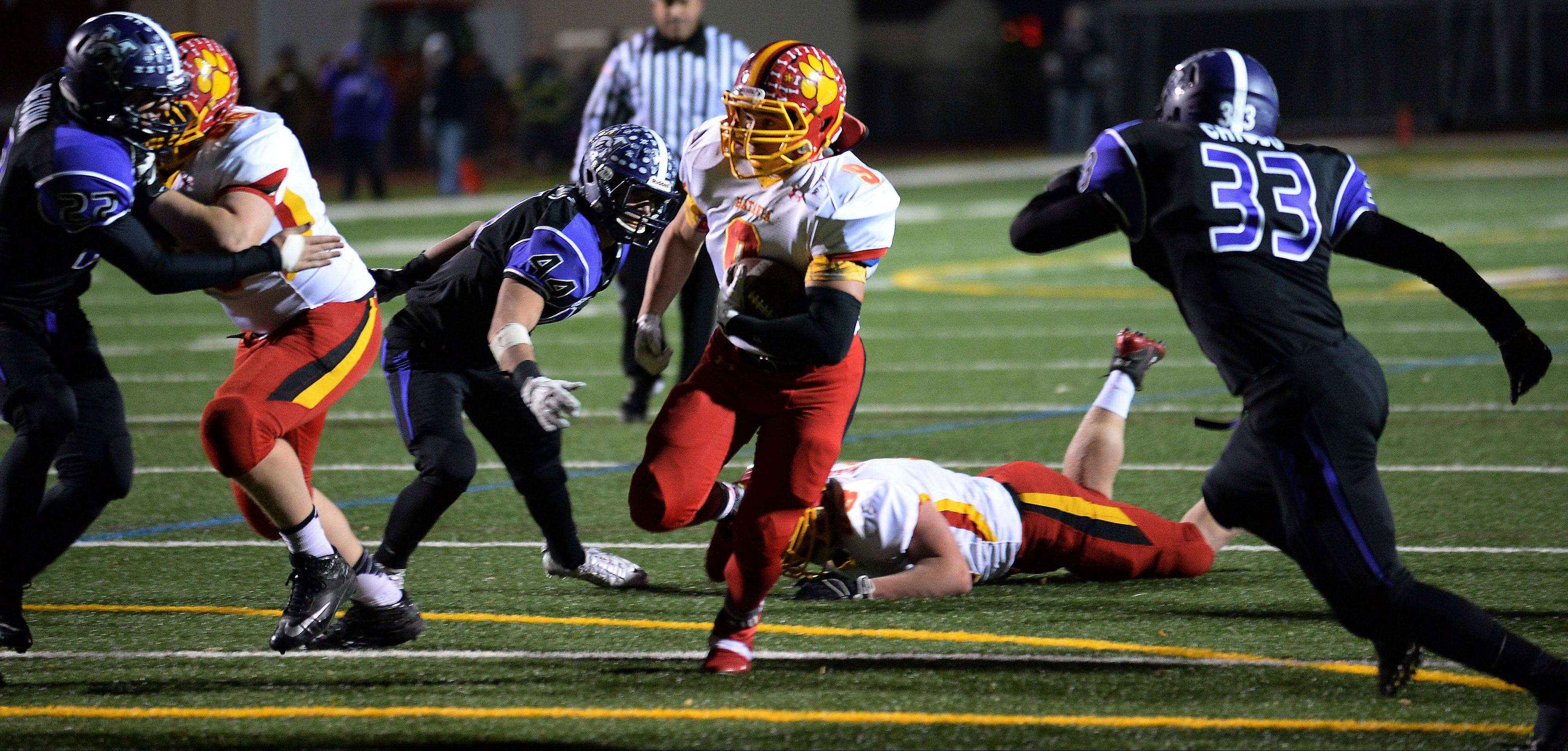 Batavia's Anthony Moneghini runs past Rolling Meadows' Nico Chiodo in the fourth quarter for a touchdown in the Bulldogs' 48-13 win last Saturday.