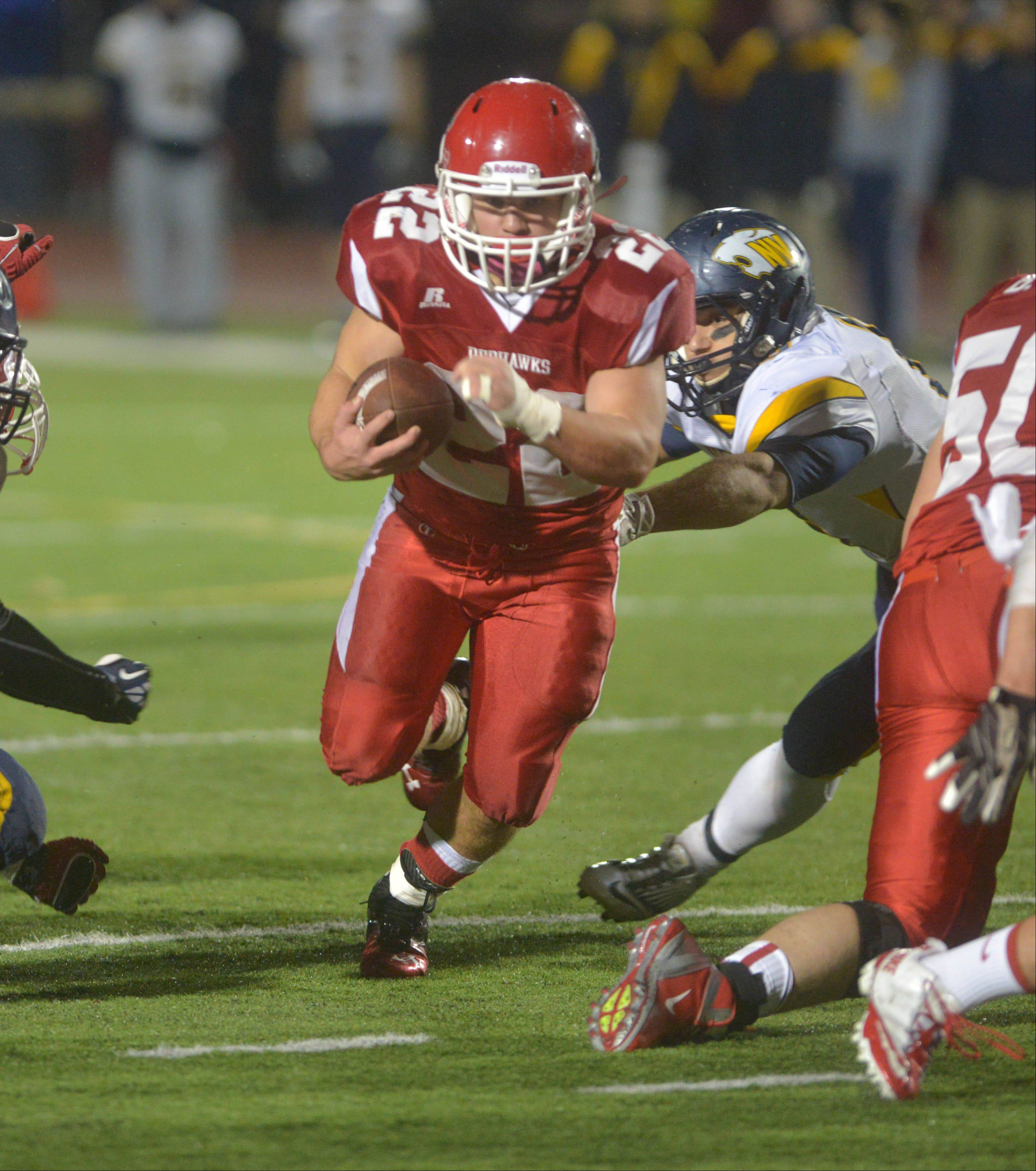 Kevin Clifford of Naperville Central picks up yardage against Neuqua Valley in Class 8A quarterfinal action Saturday.
