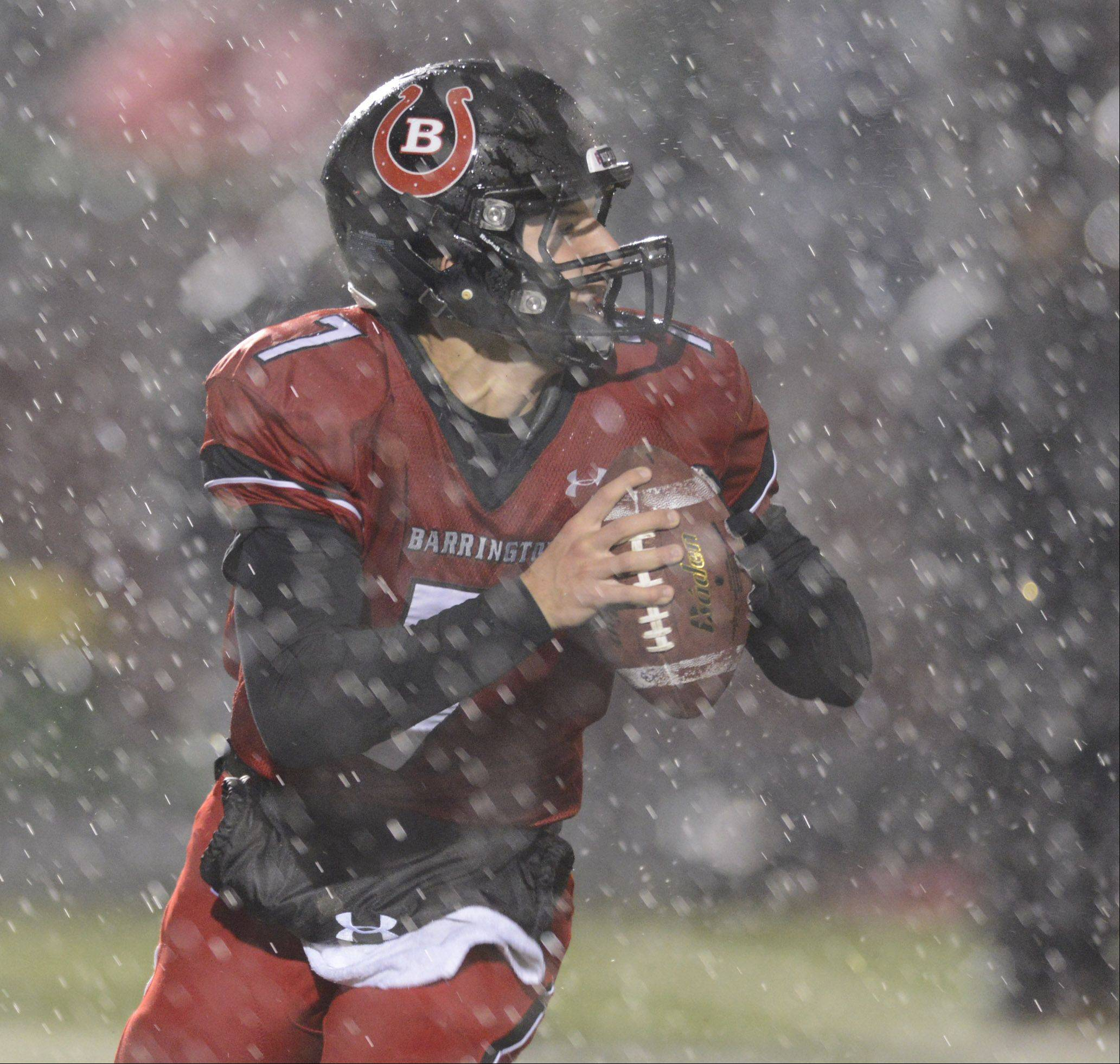 Barrington quarterback Daniel Kubiak looks to pass in pouring rain during Saturday's football game against Stevenson.
