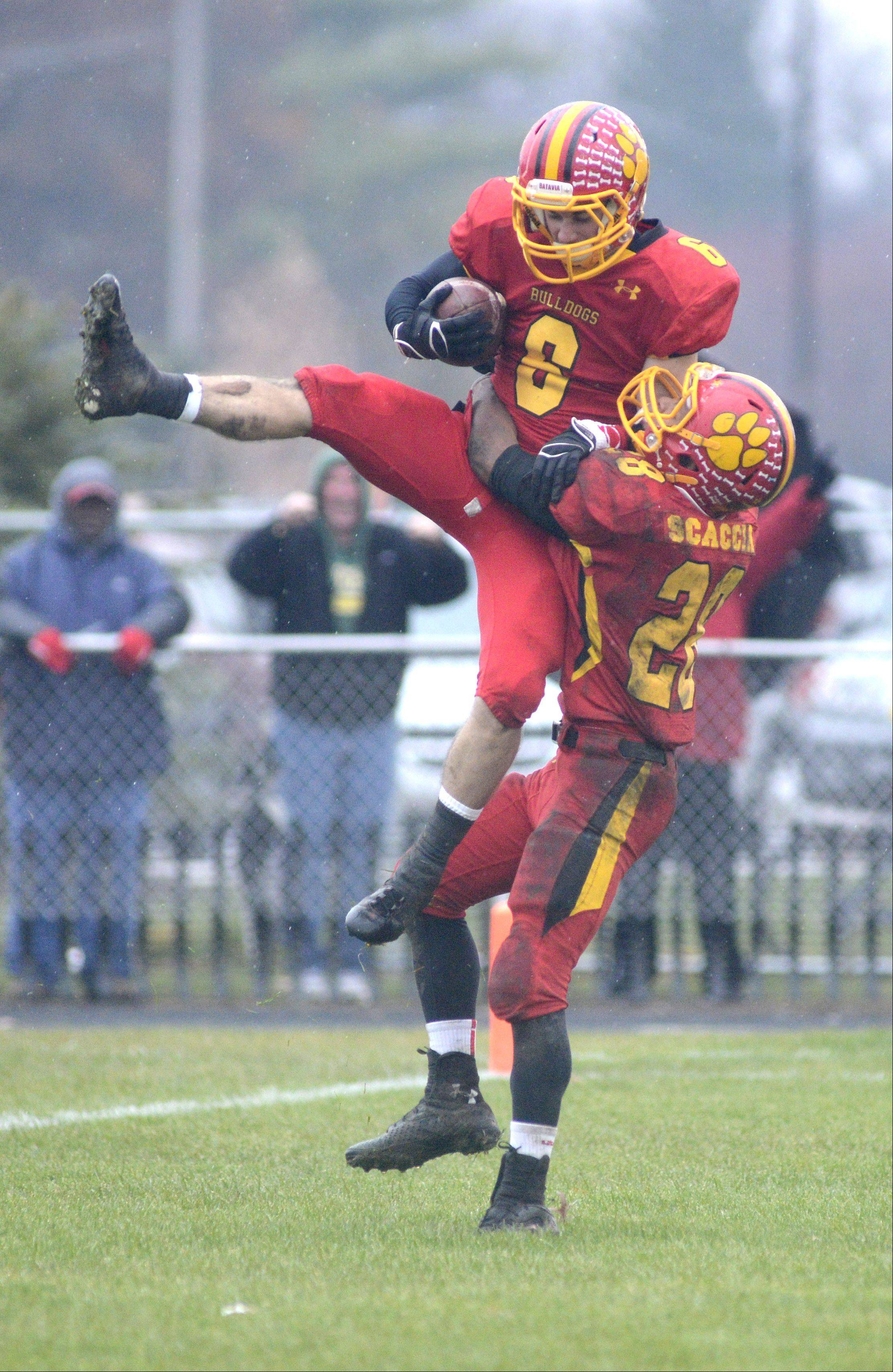 Batavia's Rouke Mullins is hoisted into the air by teammate Anthony Scaccia after scoring a touchdown in the third quarter over Lake Forest in the Class 6A quarterfinal on Saturday, November 16.