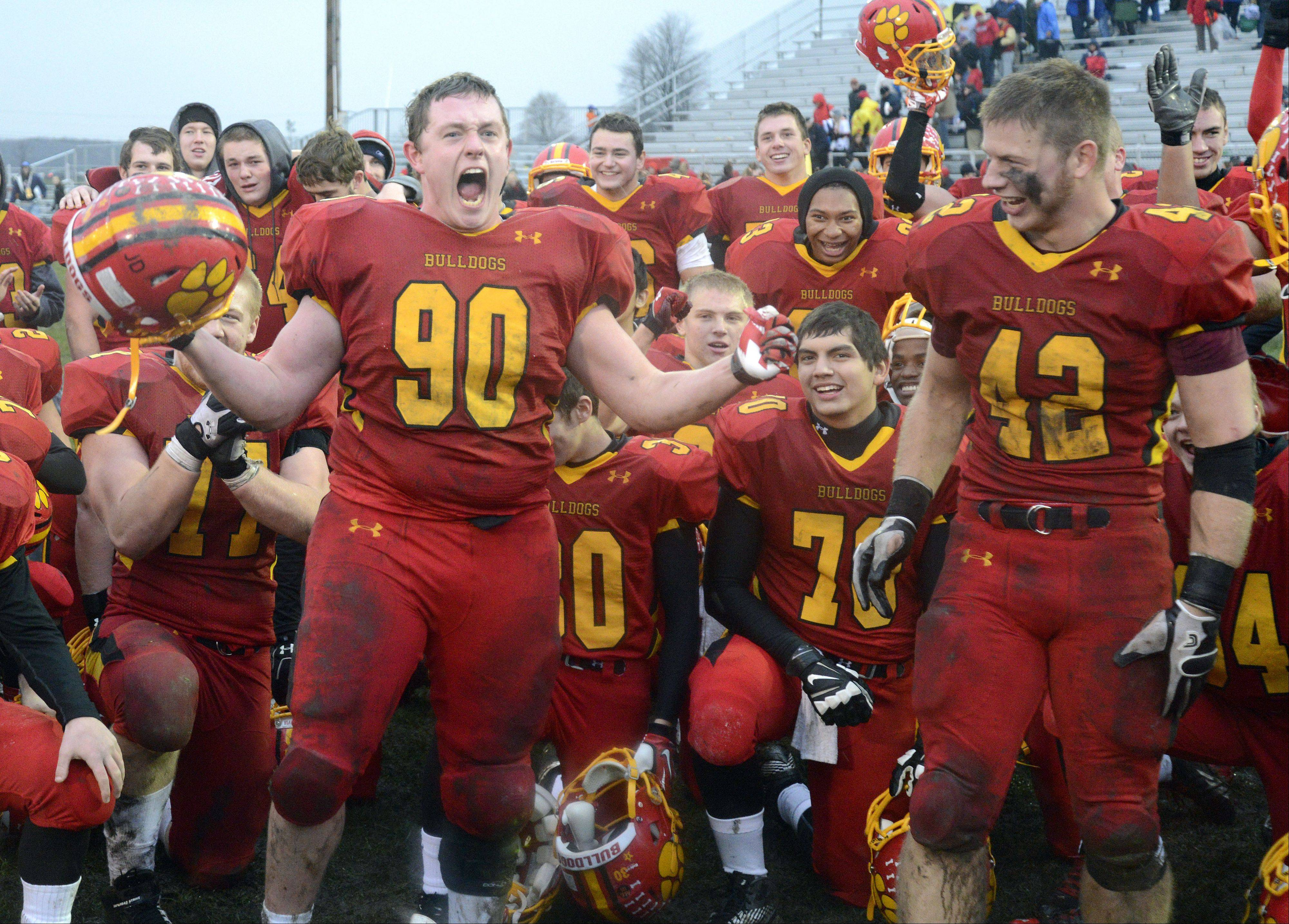 Batavia's Ryan Minniti screams in victory in the post game huddle after beating Lake Forest in the Class 6A quarterfinal on Saturday, November 16. Teammate Kevin Green on right. (42)