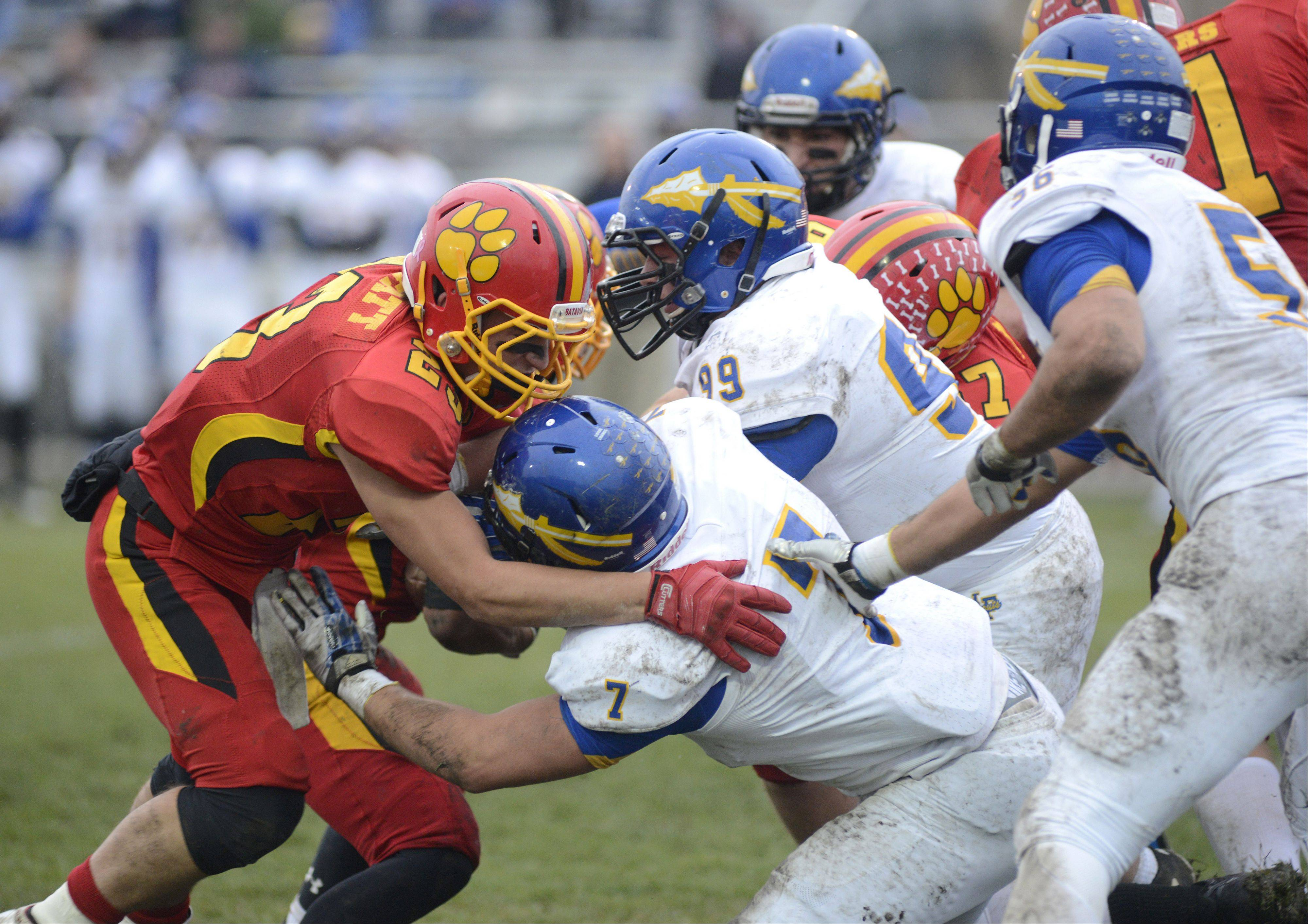 Batavia's Michael Moffatt tucks the ball as he's tackled by Lake Forest's Trent Williams (7) and Nicholas Athenson in the second quarter of the Class 6A quarterfinal on Saturday, November 16.