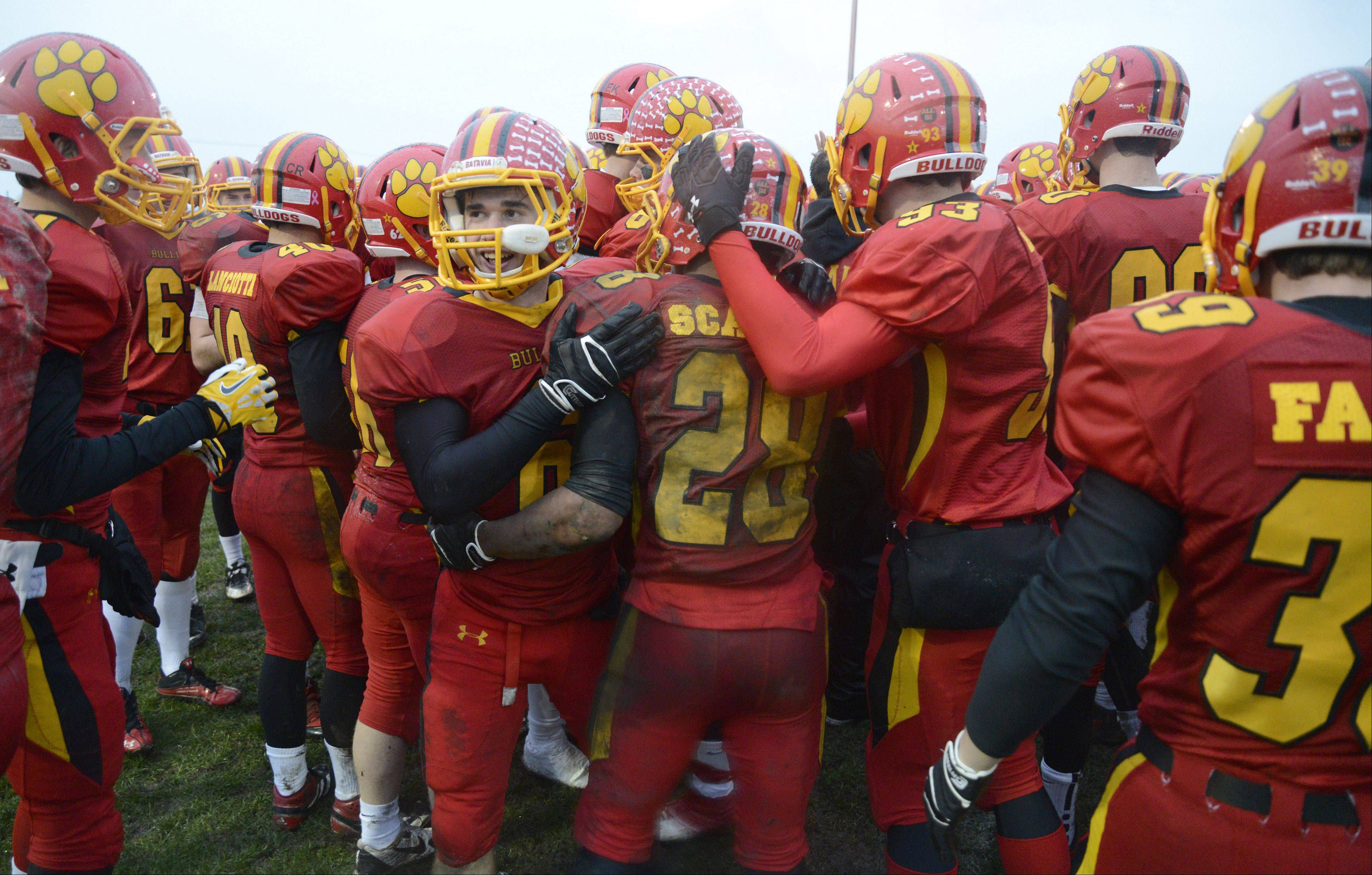 Batavia's Rourke Mullins (facing) walks away from the huddle after hugging Anthony Scaccia and Nate Kearney after their Class 6A quarterfinal victory over Lake Forest on Saturday, November 16.