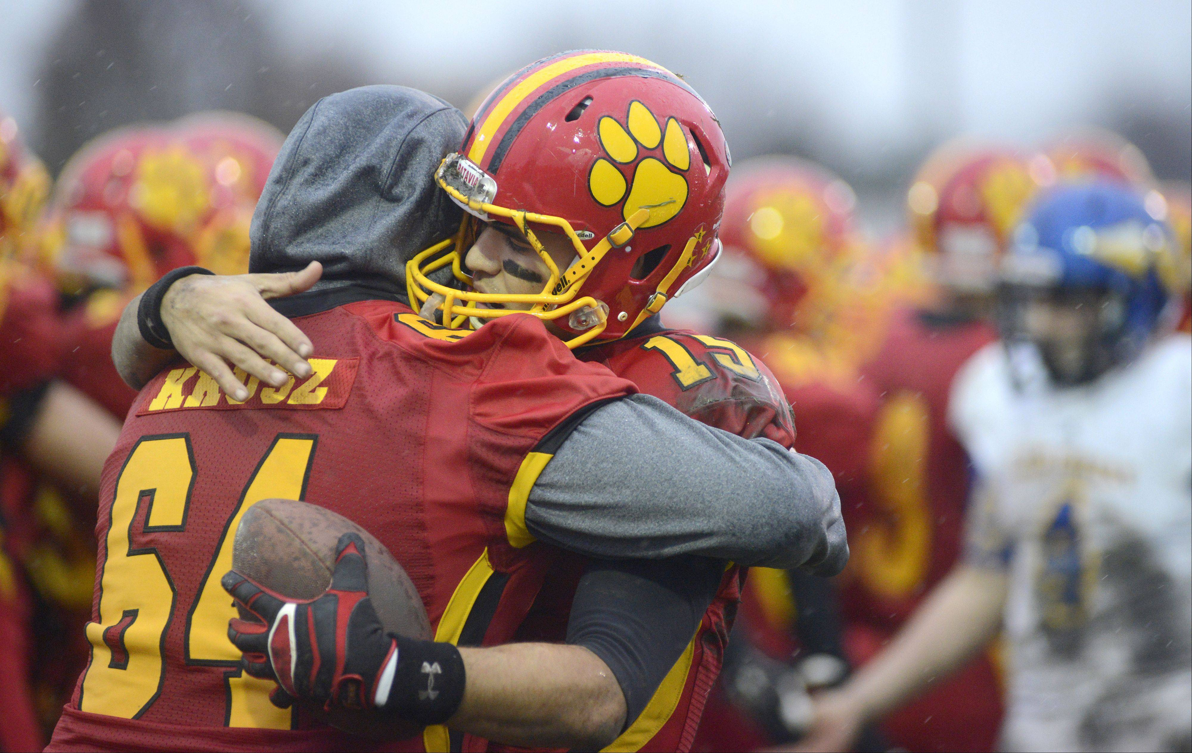 Batavia's Micah Coffey embraces sidelined teammate Mitchell Krusz after their victory over Lake Forest in the Class 6A quarterfinal on Saturday, November 16.