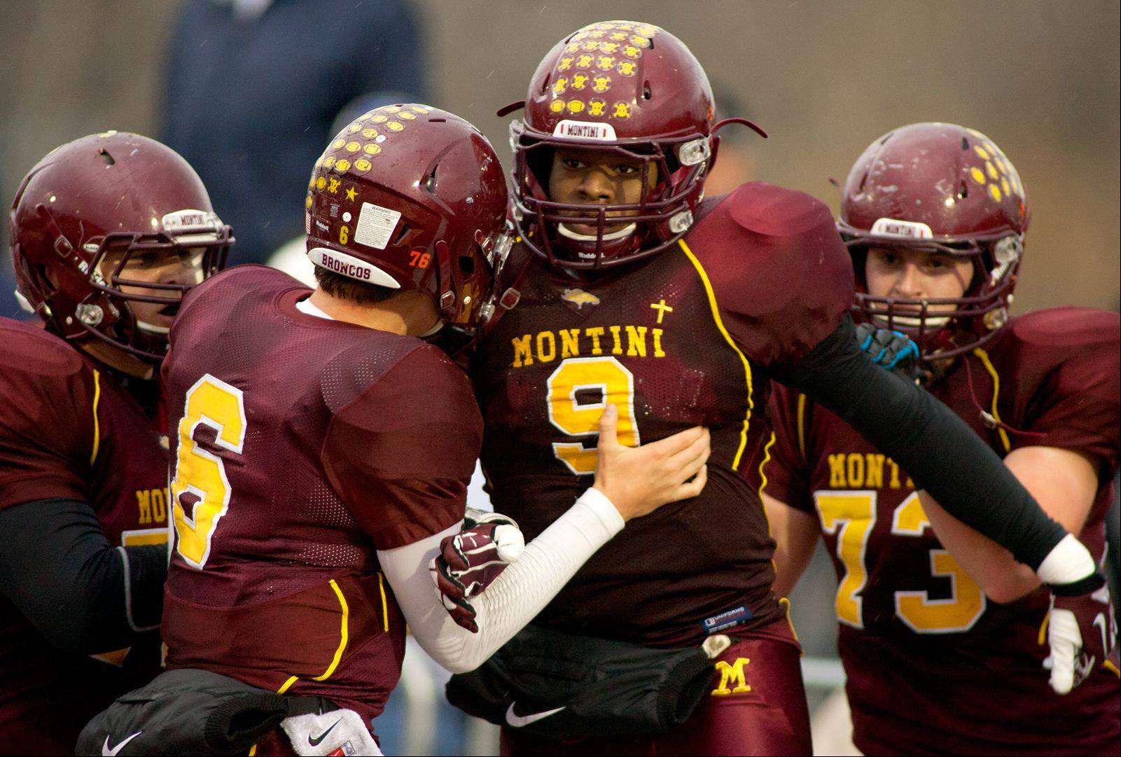 Montini Catholic's Niles Sykes (9) is mobbed by teammates after his 2-point conversion gave the Broncos a 22-21 win over Joliet Catholic.