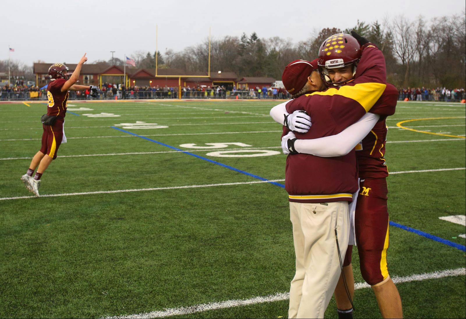 Montini Catholic's Stephen Dennis is congratulated by head coach Chris Andriano after the game. Dennis caught a deflected pass to score the game winning touchdown against Joliet Catholic.