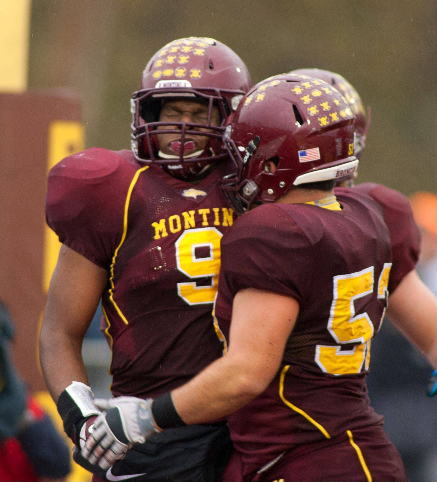 Montini Catholic's Niles Sykes (9) celebrates his second half touchdown with Anthony Ferraro, right, during a 22-21 win over Joliet Catholic.