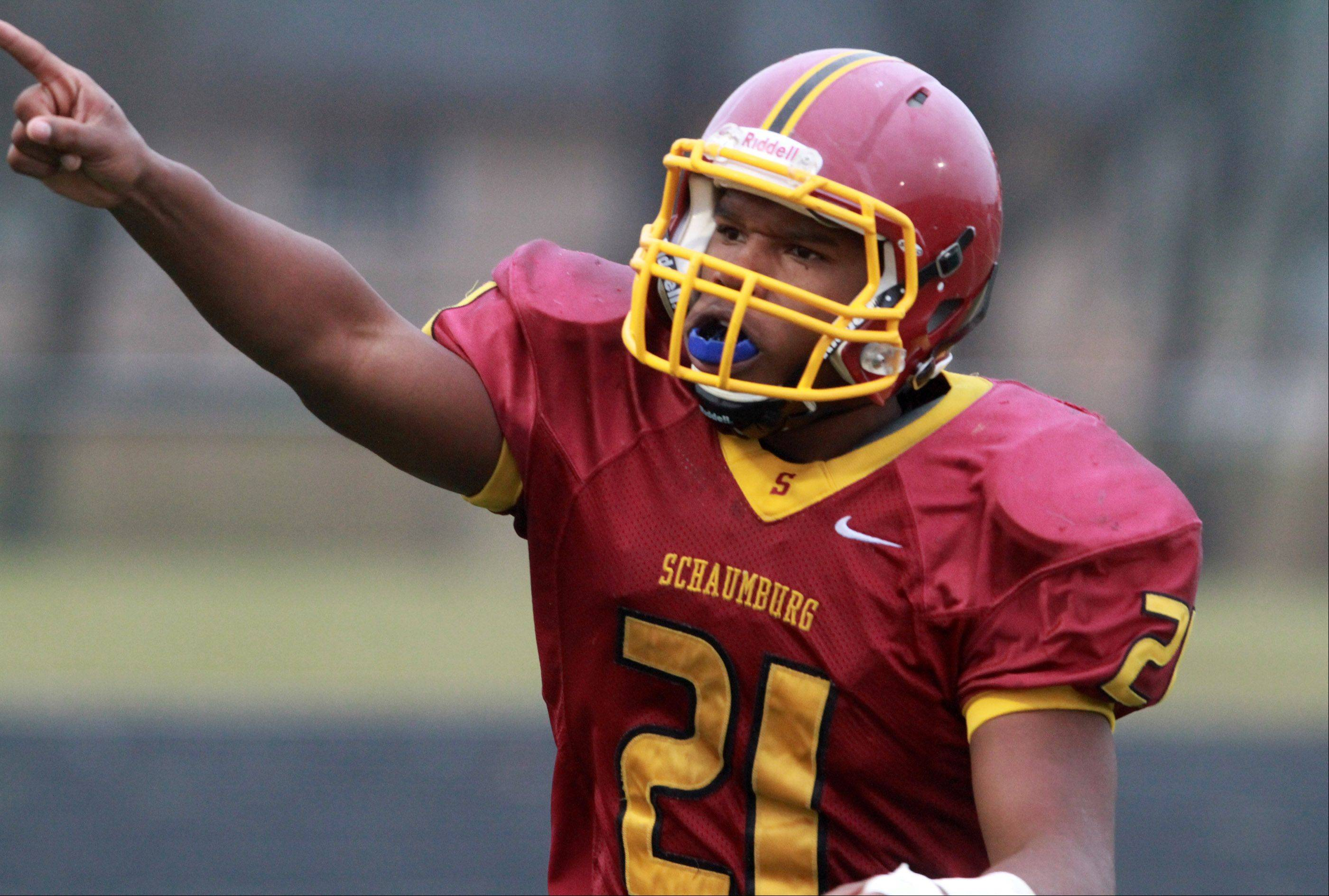 Schaumburg Justice Macneal-Young celebrates running for a touchdown against Glenbard West in a quarterfinal playoff game on Saturday in Schaumburg.