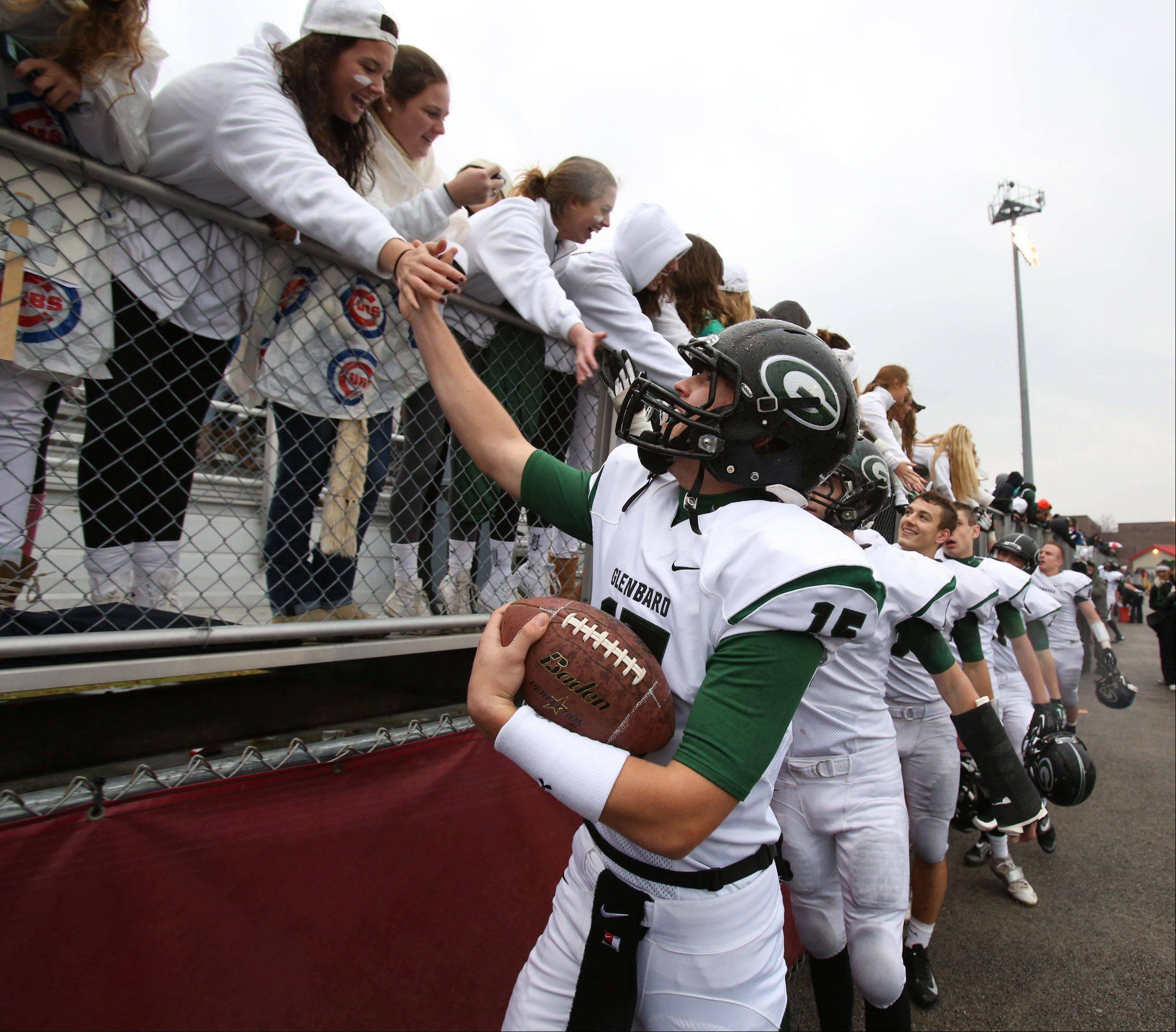 Glenbard West quarterback Kevin Dawrant celebrates with fans as Glenbard West wins 42-21 over Schaumburg in a quarterfinal playoff game on Saturday in Schaumburg.