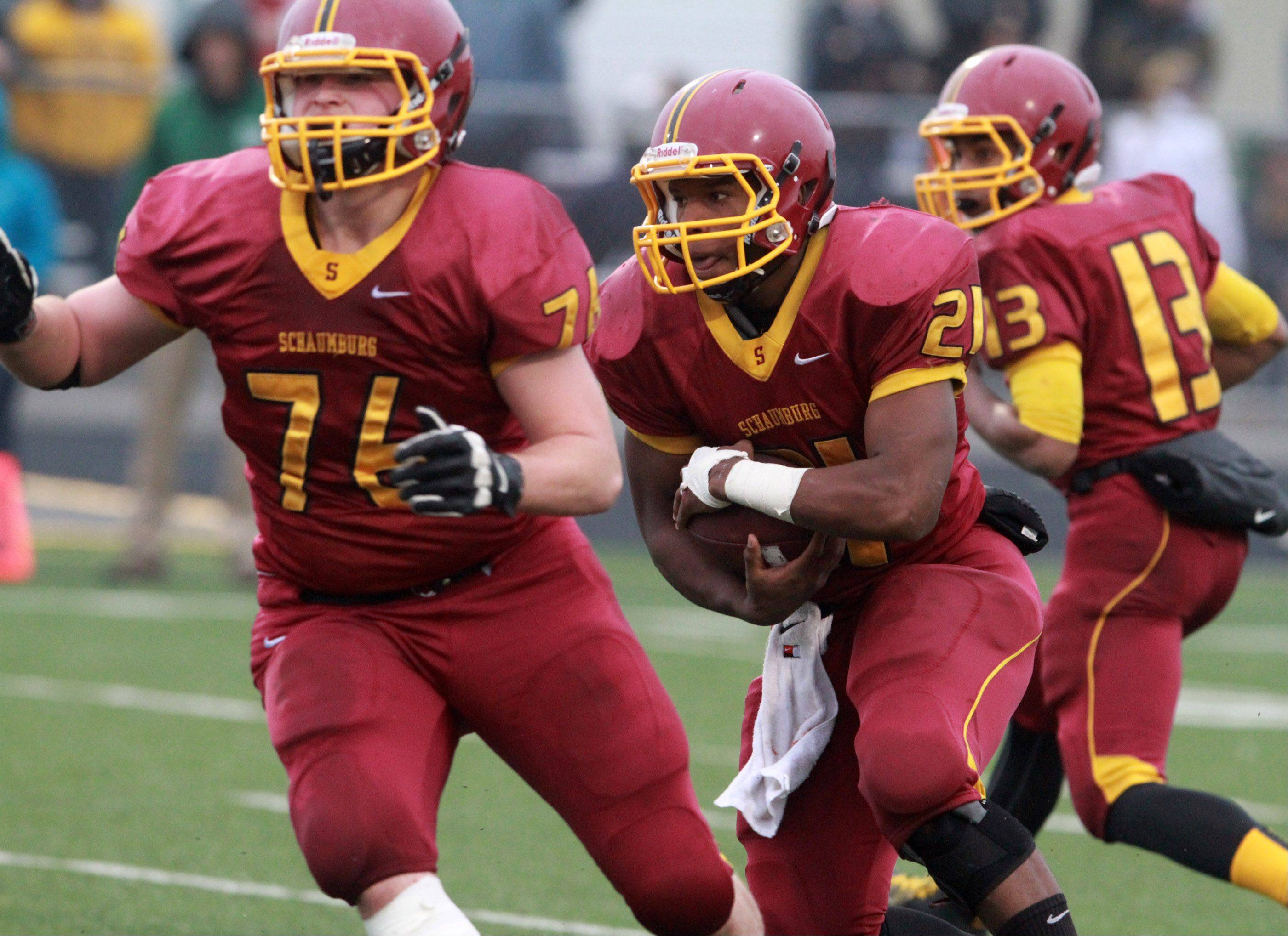 Schaumburg running back Justice Macneal-Young runs behind blocking from Aleksander Piotrowski against Glenbard West.