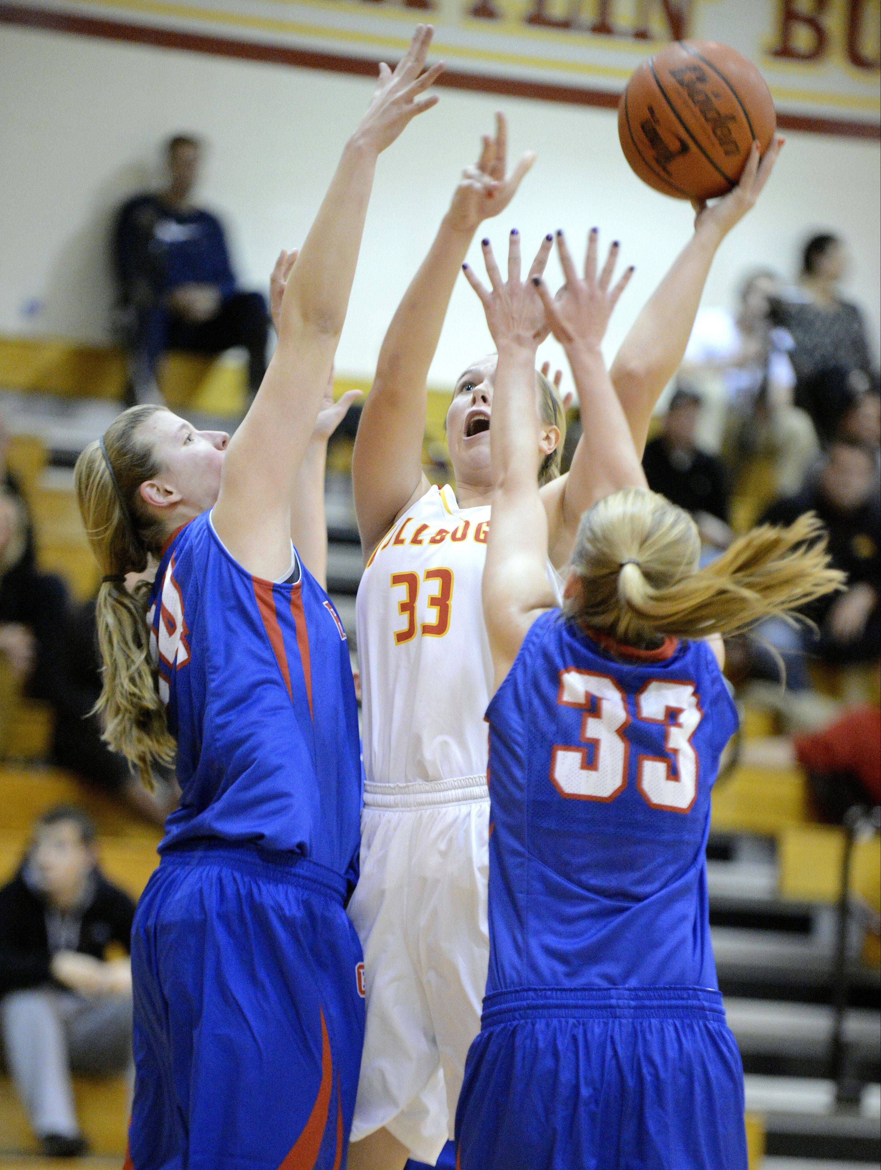 Glenbard South's Sydney Bauman and Tomei Ball swarm Batavia's Erin Bayram as she takes a shot Tuesday.