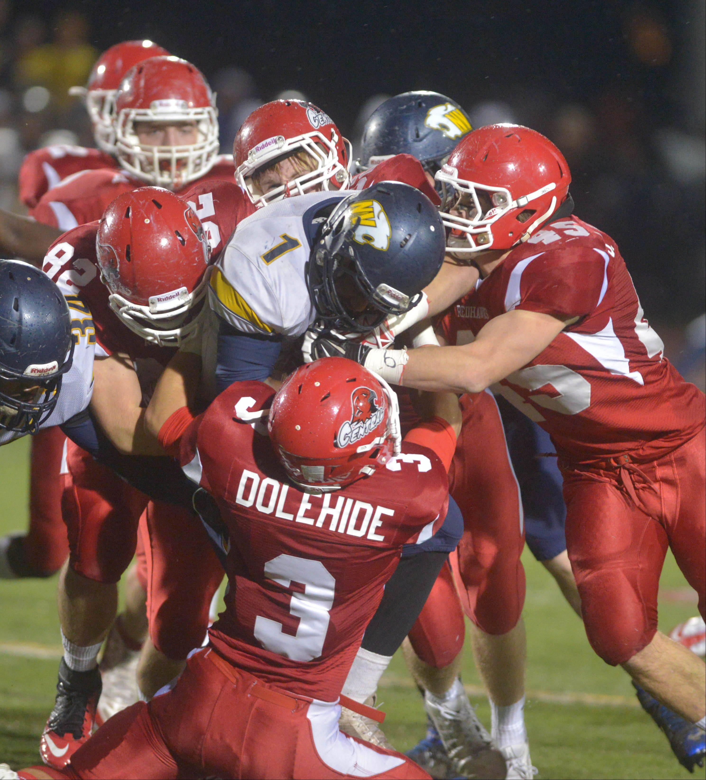 Nolan Dean of Neuqua is pulled down by Naperville Central defenders during the Neuqua Valley at Naperville Central Class 8A football quarterfinal Saturday.