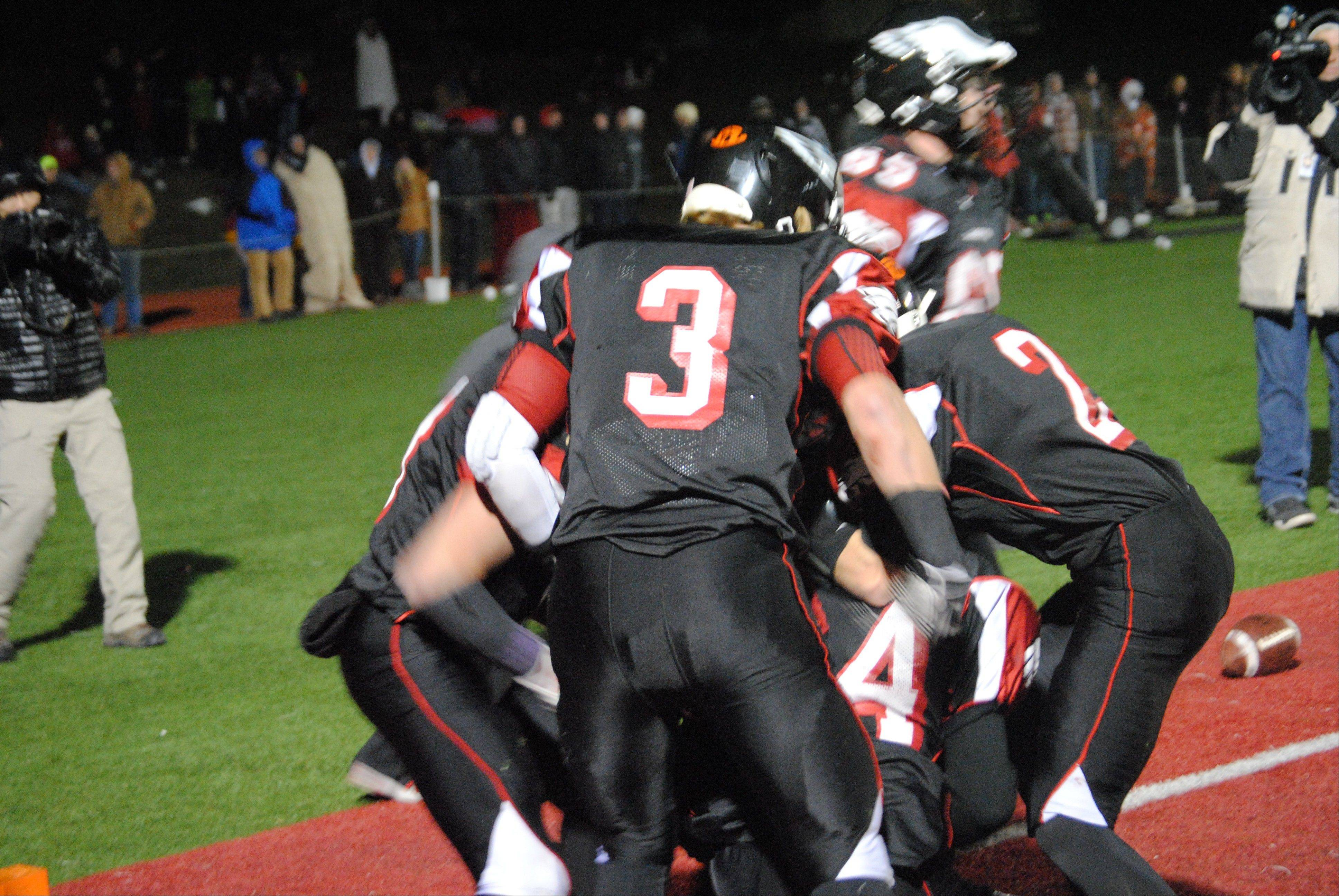 Aurora Christian tailback Legend Smith (44) getting mobbed by jubilant teammates after his 10-yard TD reception that gave the Eagles a 26-21 lead over Stillman Valley with 2:27 remaining during Saturday's 3A state semifinals in Aurora. Stillman Valley rallied for a 28-26 win.