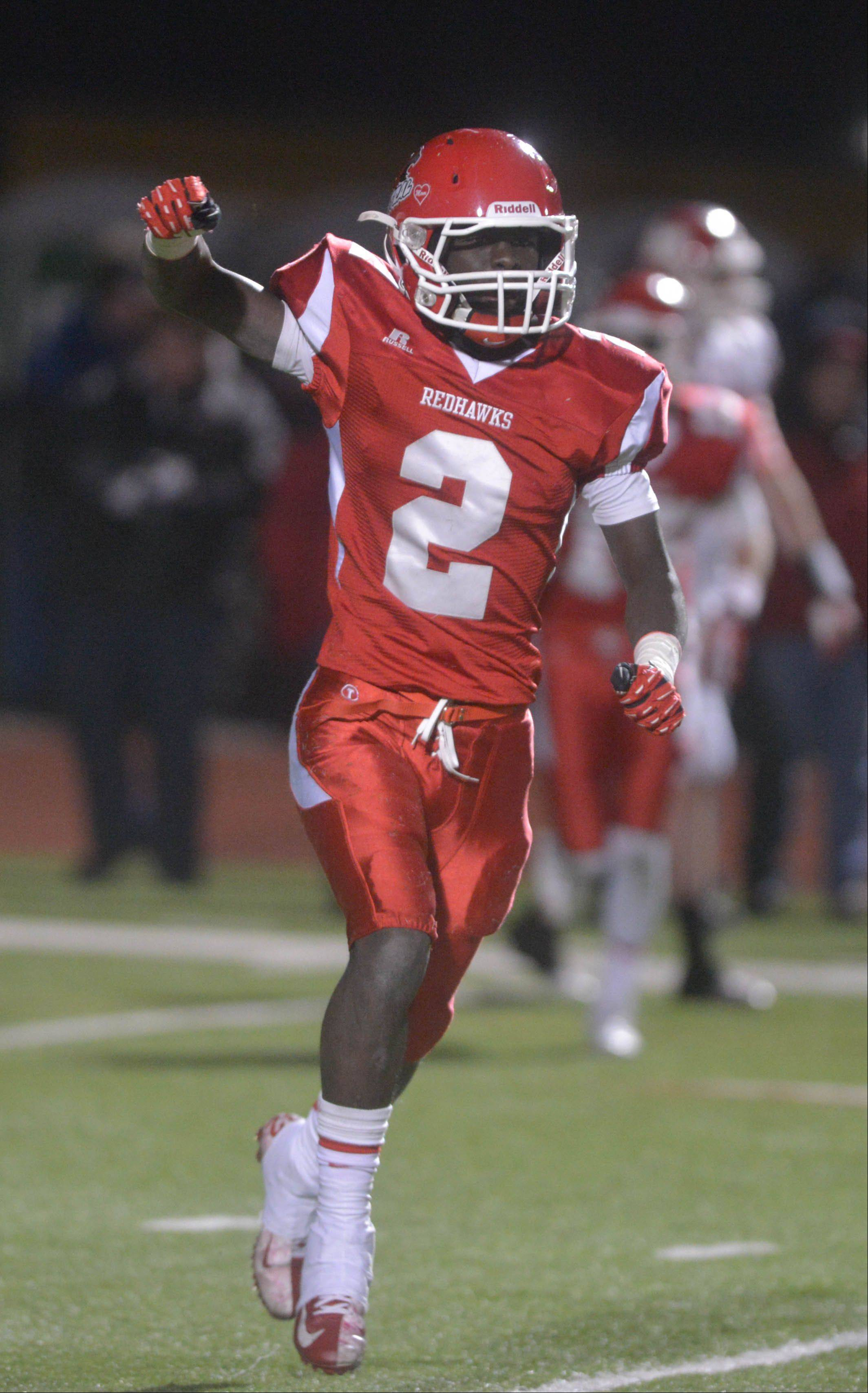 Jon Lubanza of Naperville Central celebrates an interception during the Marist at Naperville Central Class 8A semifinal Saturday.