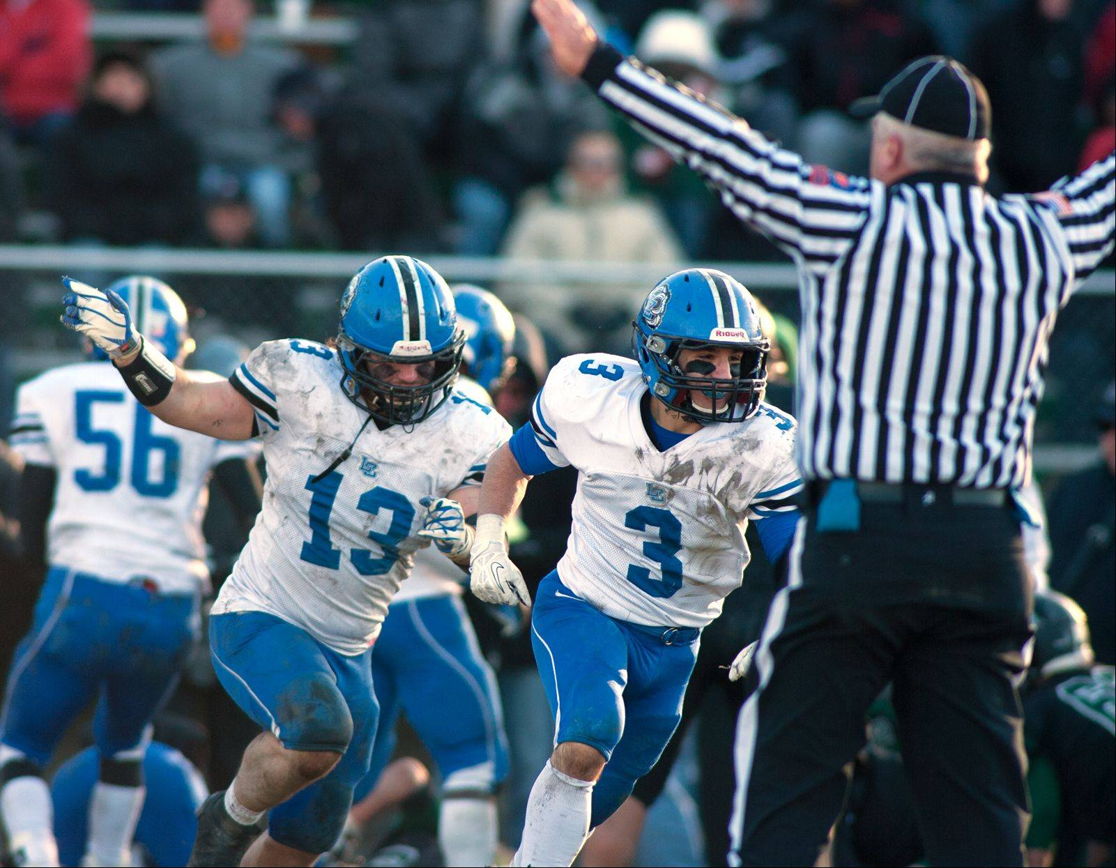 Lake Zurich defensive end Chris Lehtinen (13) and cornerback Dominic Scaduto (3) celebrate a turnover during Saturday's Class 7A state semifinal at Glenbard West.
