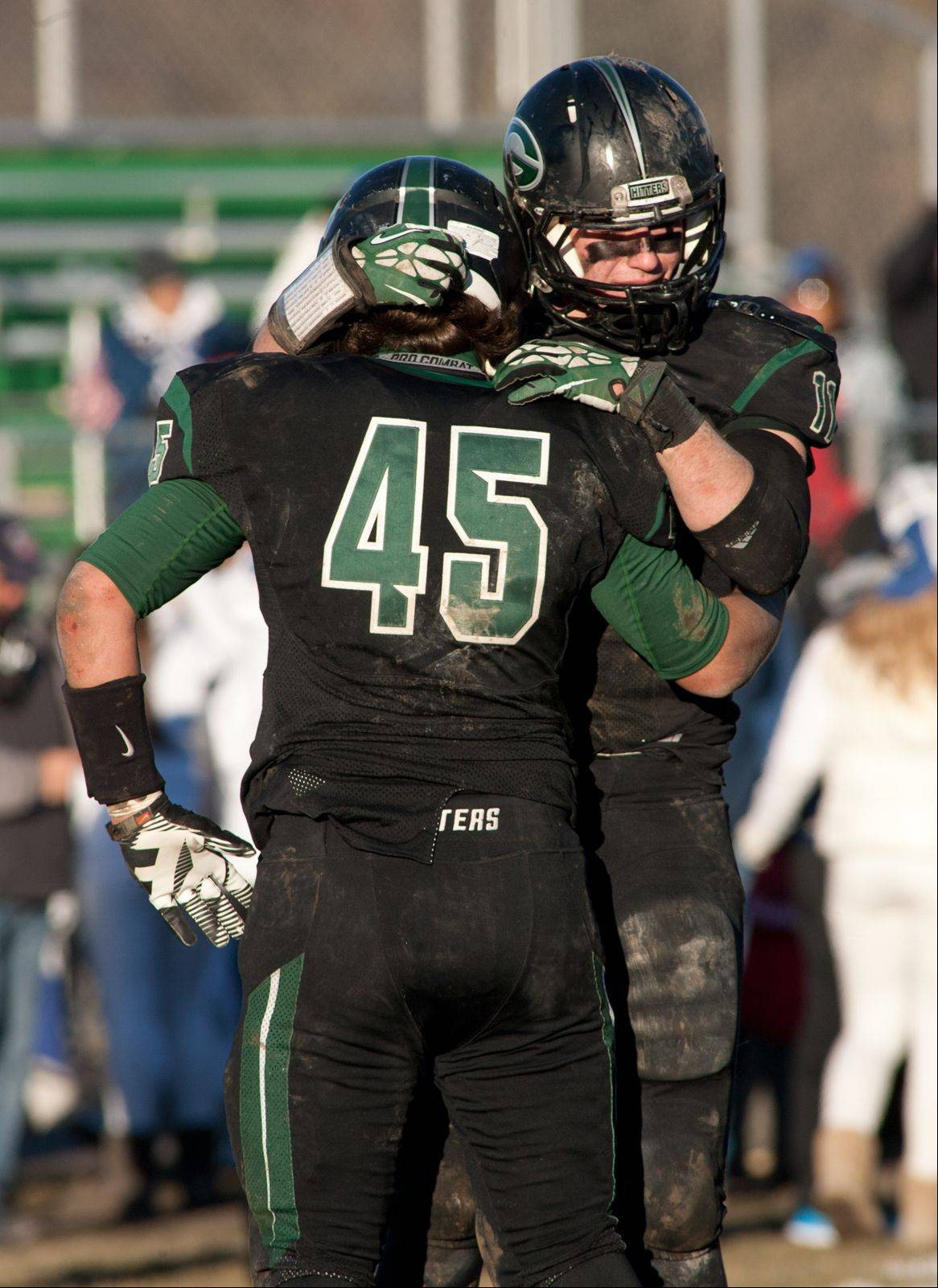 Glenbard West's Jordan Hassan (45) and Grant Greeno meet at midfield following their 16-7 loss to Lake Zurich.