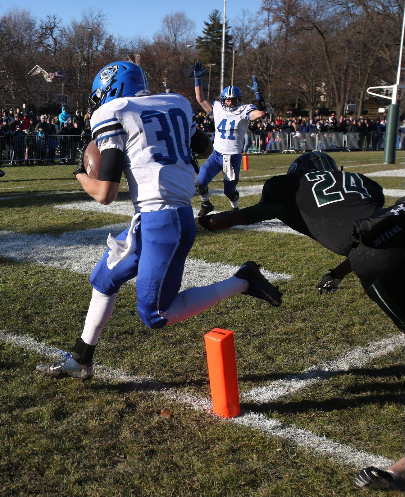 Lake Zurich's Ben Klett scores the first Bears touchdown past Glenbard West's Ryan Thomas during the Class 7A Semifinal Football Playoffs in Glen Ellyn. The Bears Colton Wagner (41), signals the call.