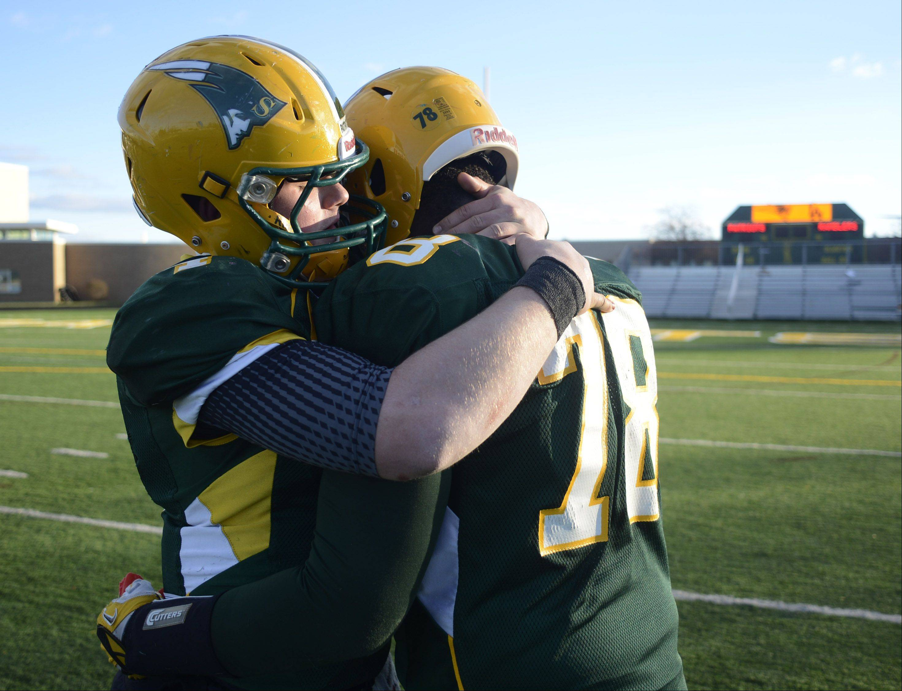 Stevenson's Willie bourbon, left, hugs teammate Nick Dillon following the Patriots' 15-14 loss to Loyola during Saturday's class 8A semifinal in Lincolnshire.