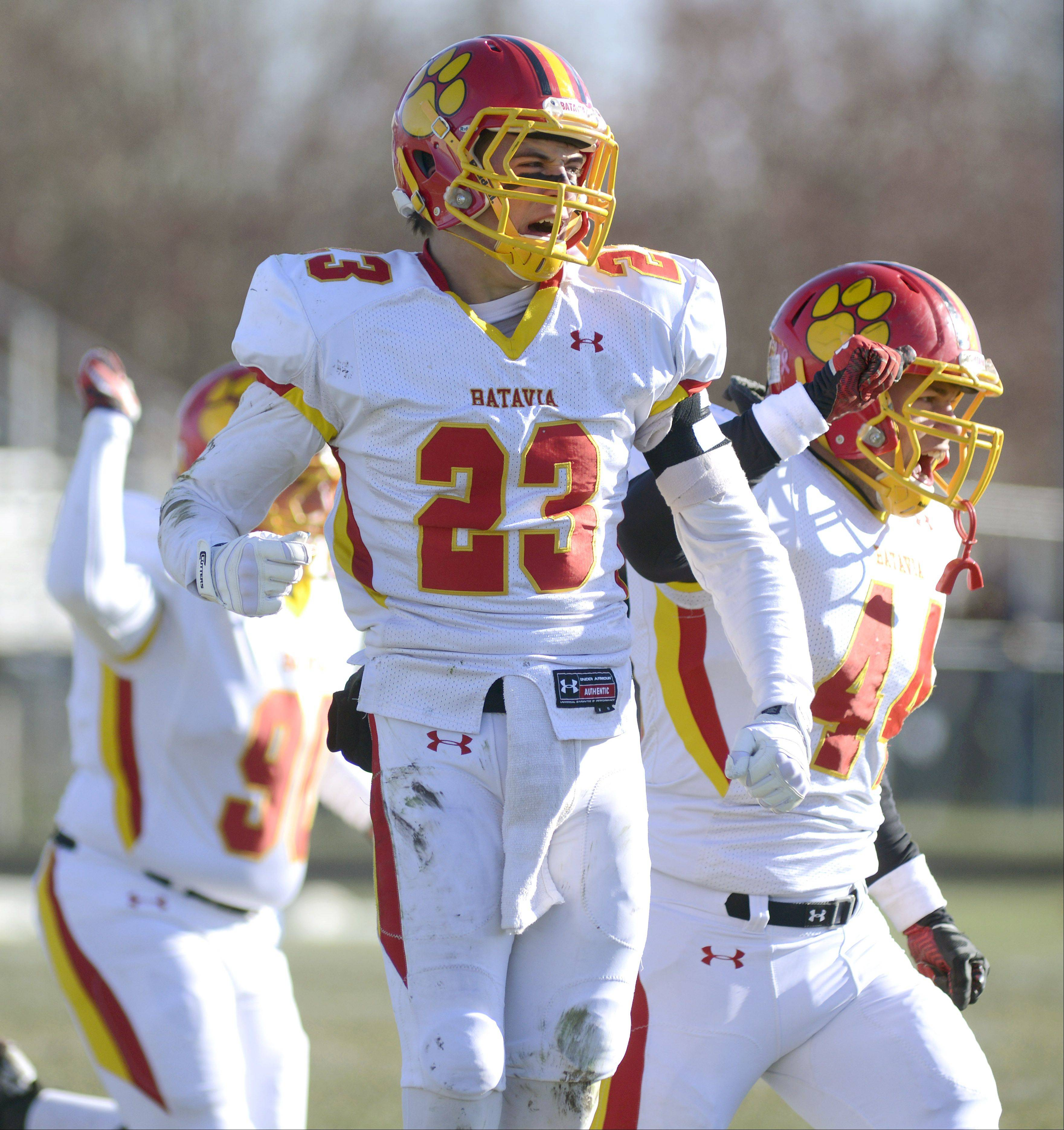Batavia's Michael Moffatt (23) and Noah Frazier (44) celebrate a Rockford Boylan fumble recovered by the Bulldogs in the first quarter of the Class 6A semifinal game on Saturday, November 23.