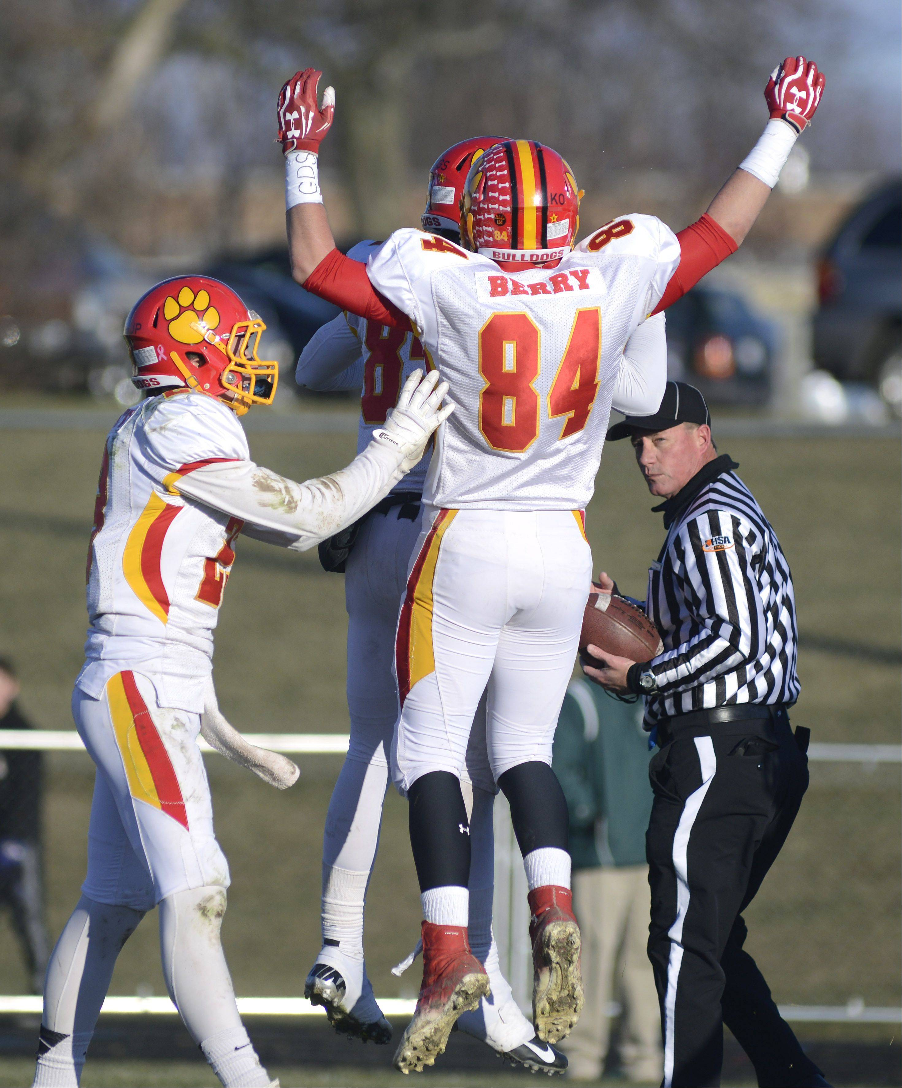 Batavia's Michael Moffatt, left, congratulates Jordan Zwart (hidden) as he bumps with Alec Berry after scoring a touchdown in the fourth quarter of the Class 6A semifinal game on Saturday, November 23.