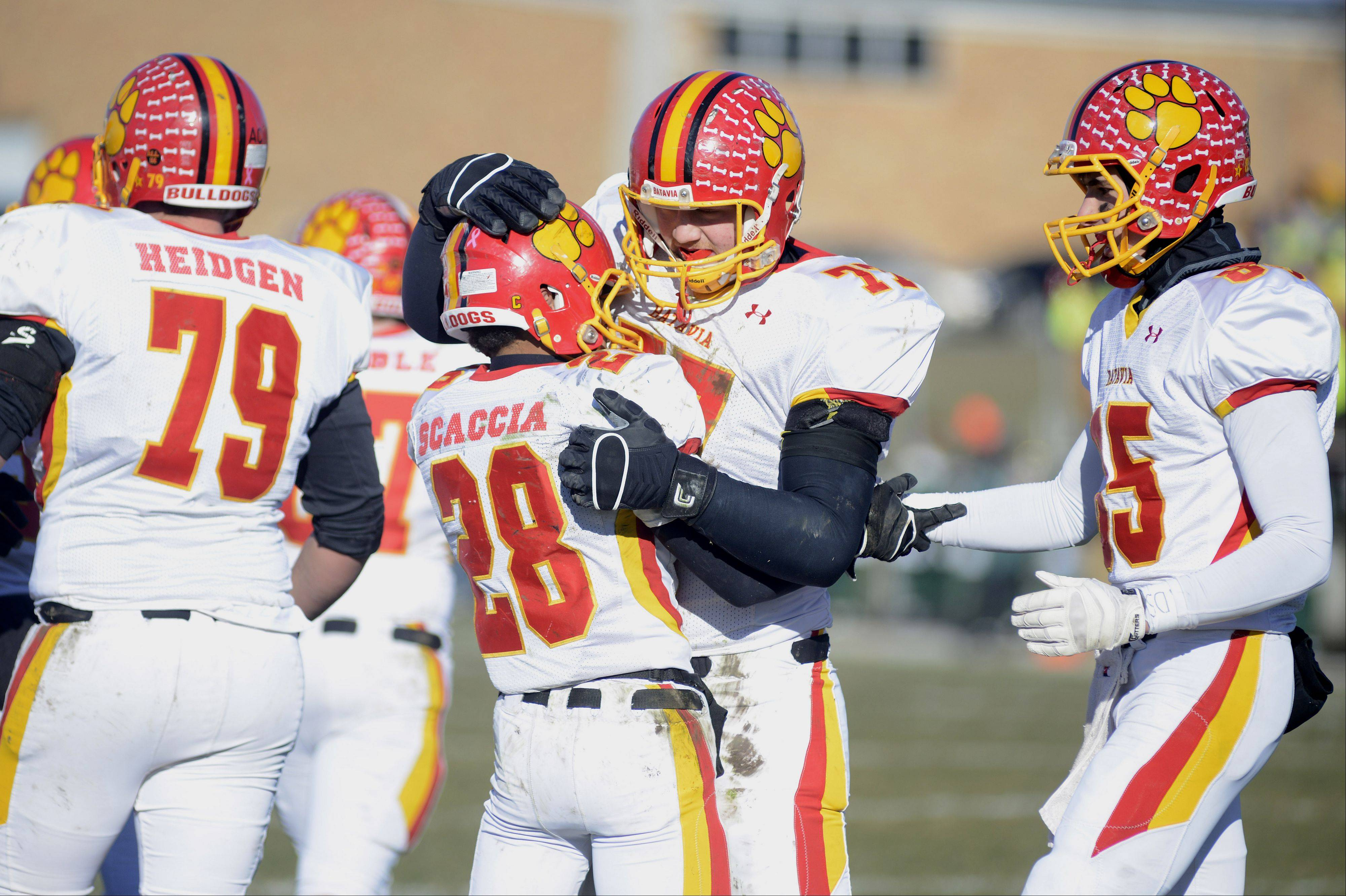 Batavia's Anthony Scaccia is congratulated by teammates Jack Breshears (77) and Jordan Zwart after scoring a touchdown in the second quarter of the Class 6A semifinal game on Saturday, November 23.