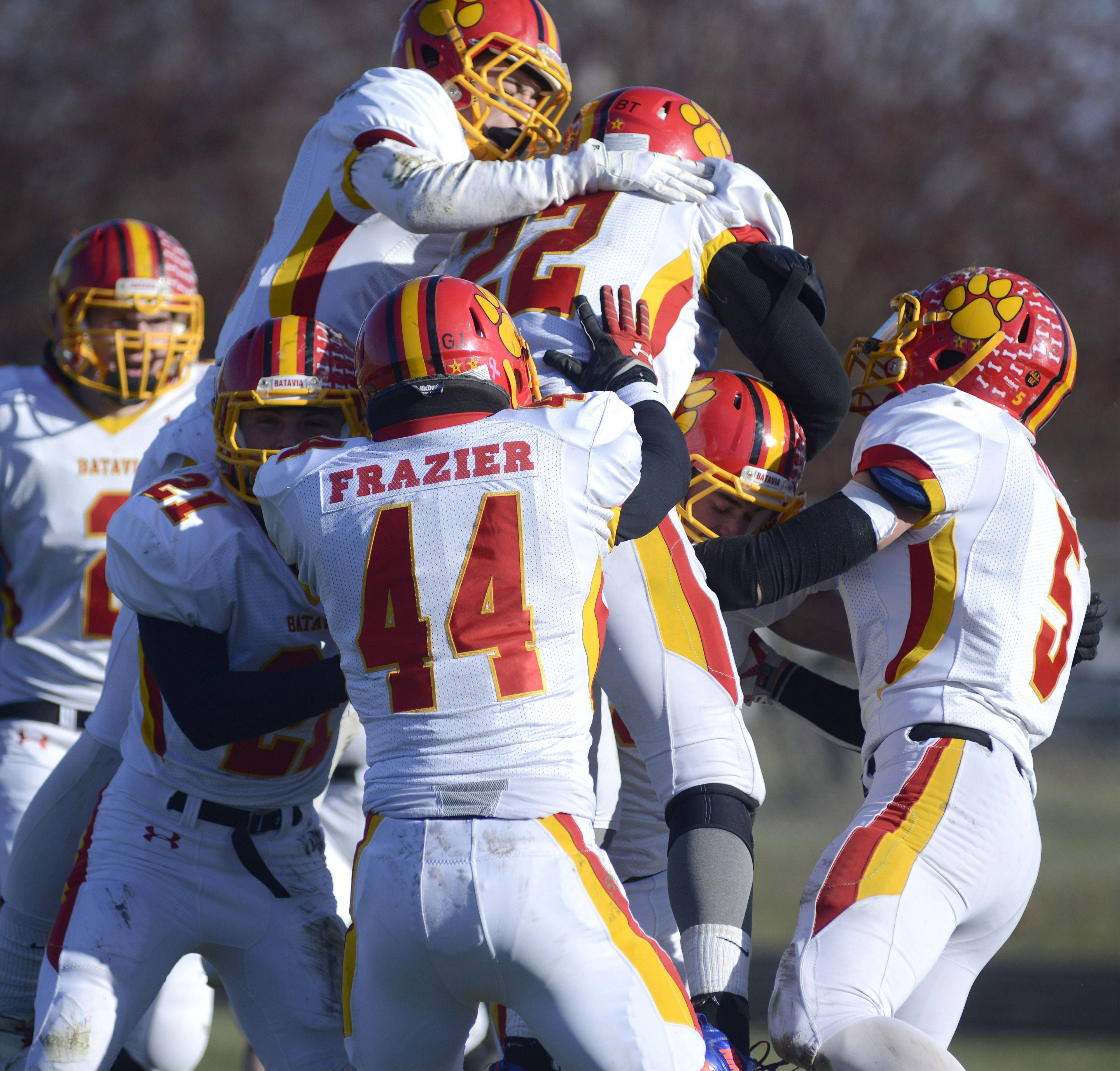 Batavia's Rourke Mullins is buried in a group celebration after scoring a touchdown on an interception in the second quarter of the Class 6A semifinal game vs. Rockford Boylan on Saturday, November 23.