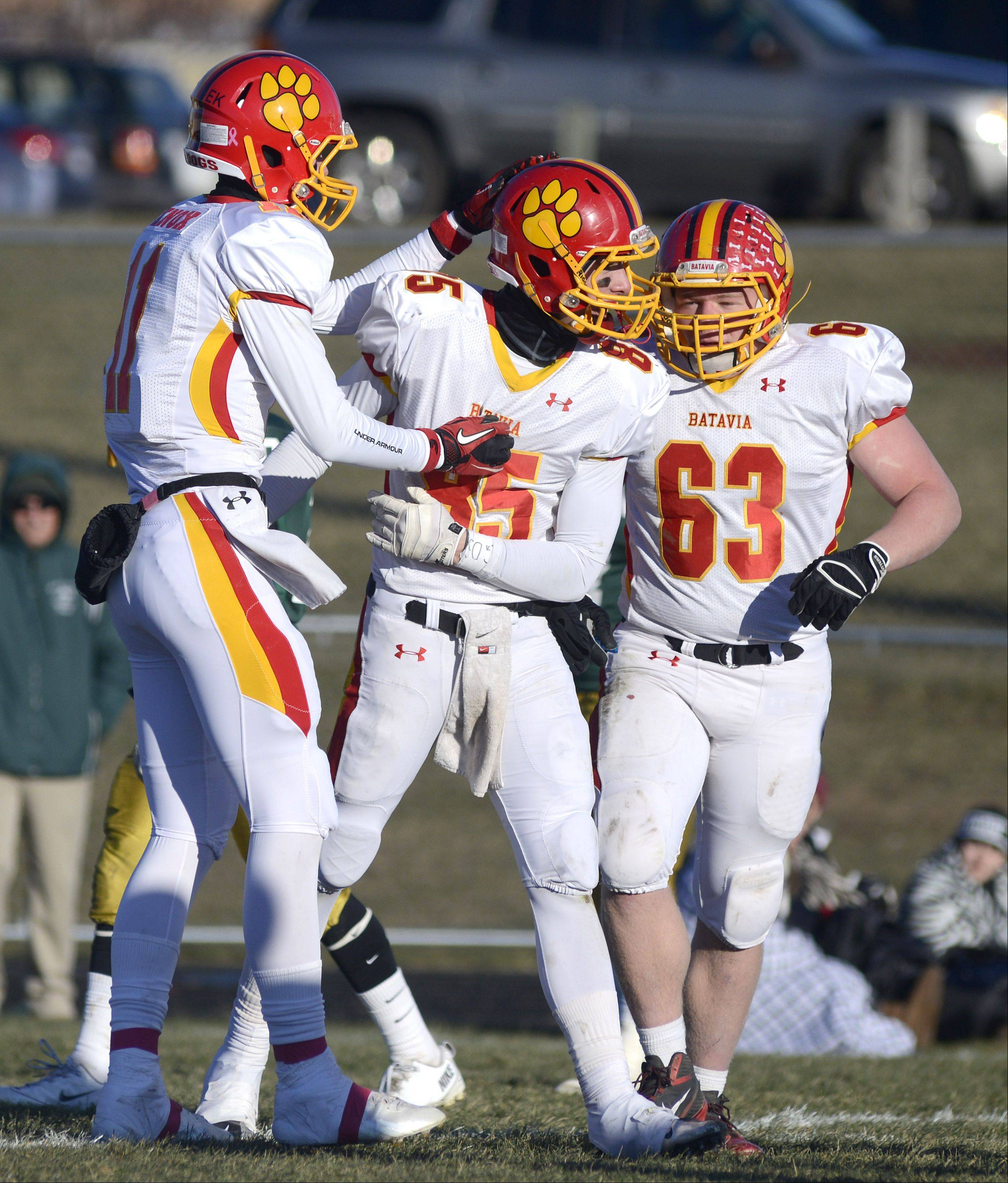 Batavia's Tucker Knox, left, and Connor McKeehan, right, congratulate teammate Jordan Zwart, center, on his touchdown in the fourth quarter of the Class 6A semifinal game on Saturday, November 23.