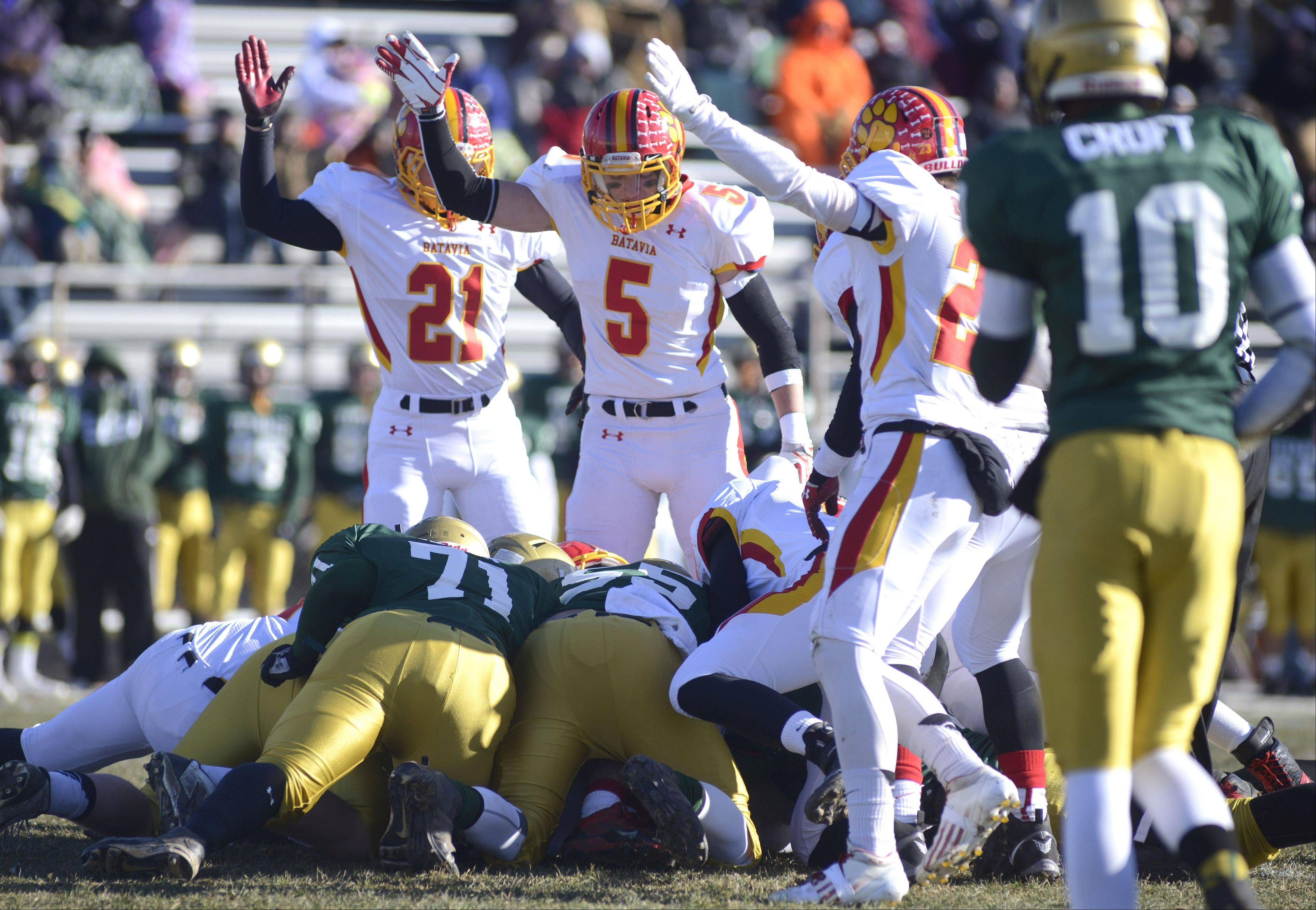 Batavia's Nick Bernabei (21), Jake Hlava (5) and Michael Moffatt point signaling the Bulldogs have recovered a Rockford Boylan fumble in the first quarter of the Class 6A semifinal game on Saturday, November 23.