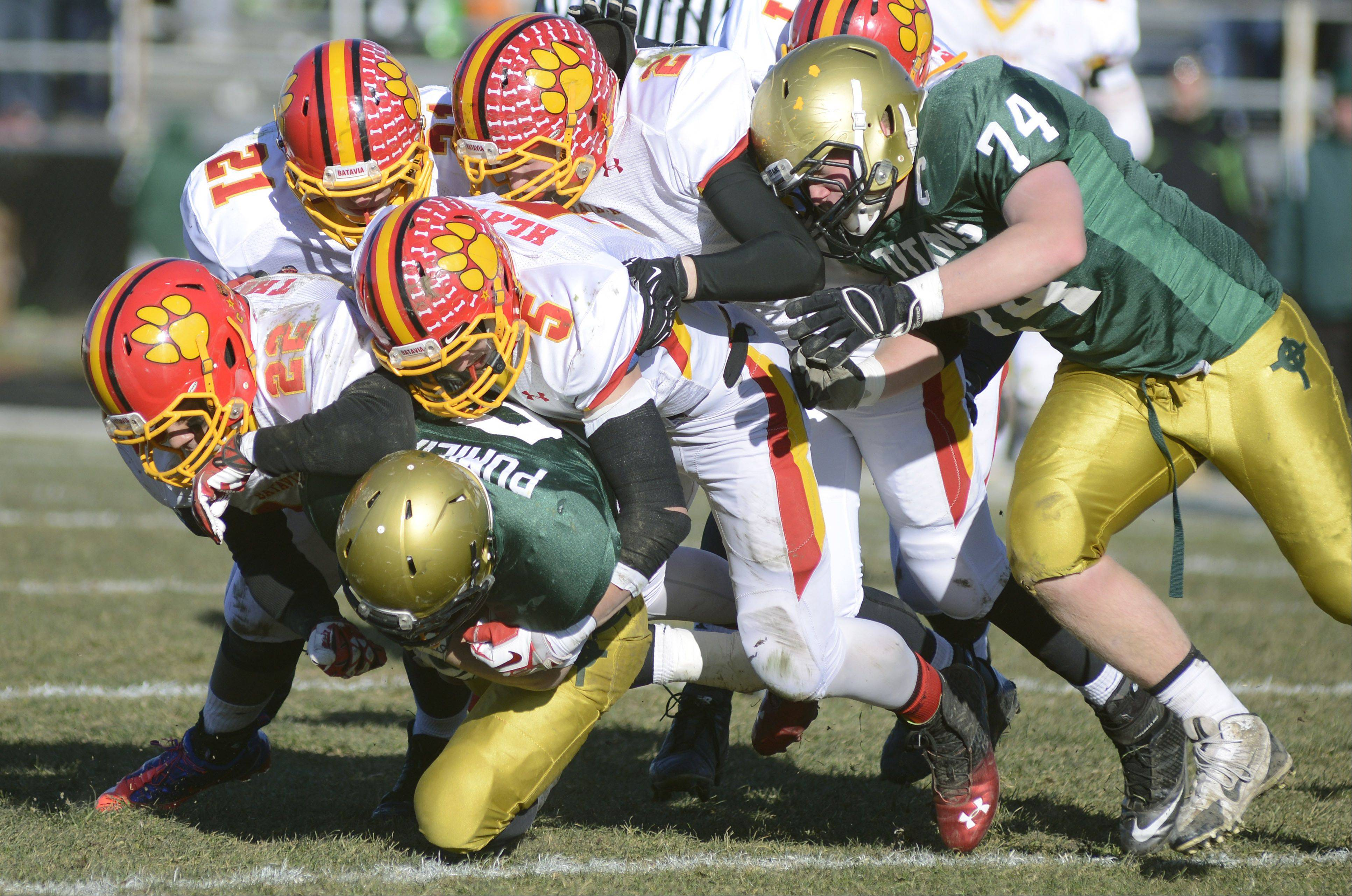 A pack of Batavia Bulldogs take down Rockford Boylan's Nick Pumilia in the second quarter of Saturday's Class 6A semifinal game in Rockford.