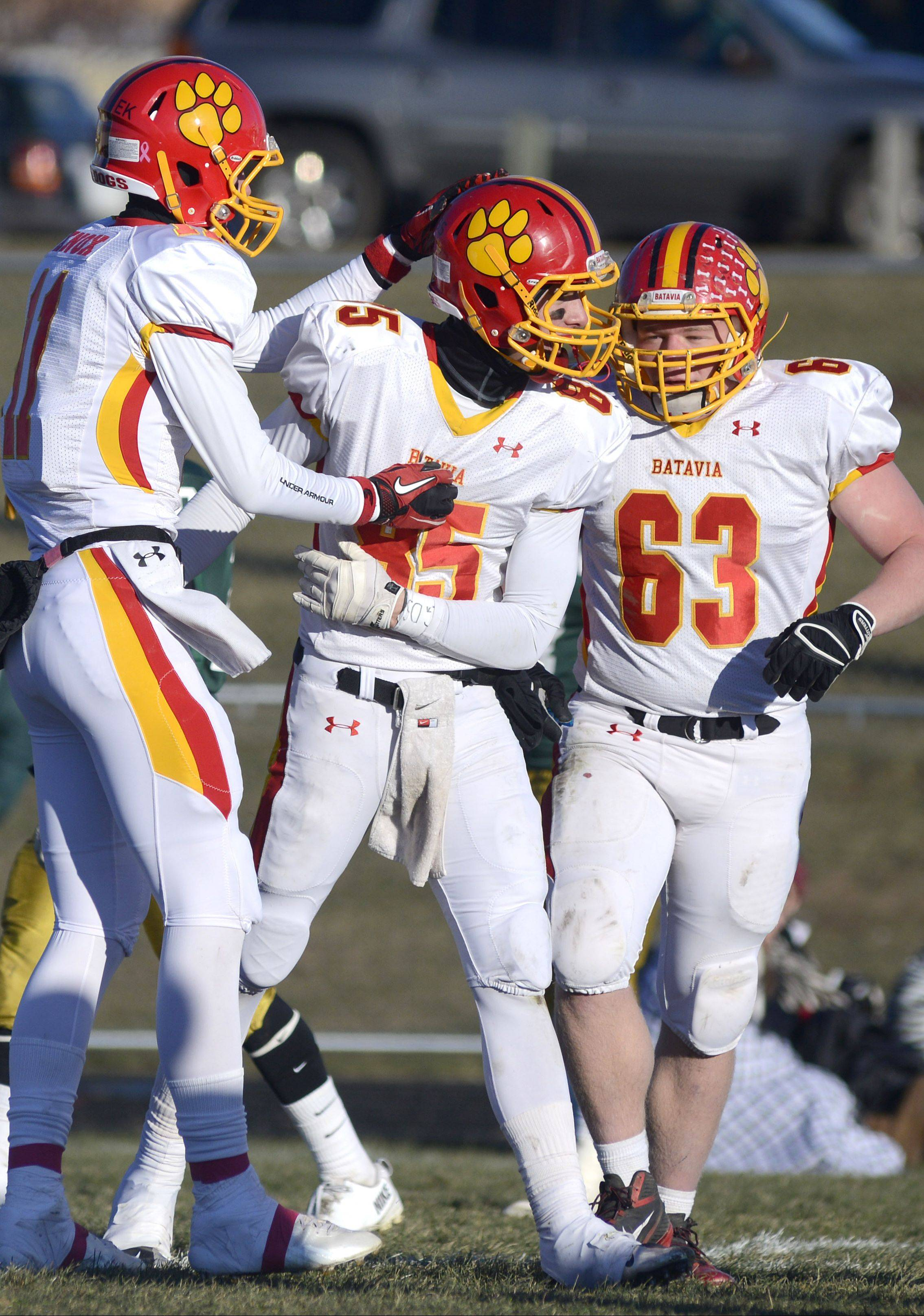 Batavia's Tucker Knox, left, and Connor McKeehan, right, congratulate teammate Jordan Zwart, center, on his 90-yard touchdown in the fourth quarter.