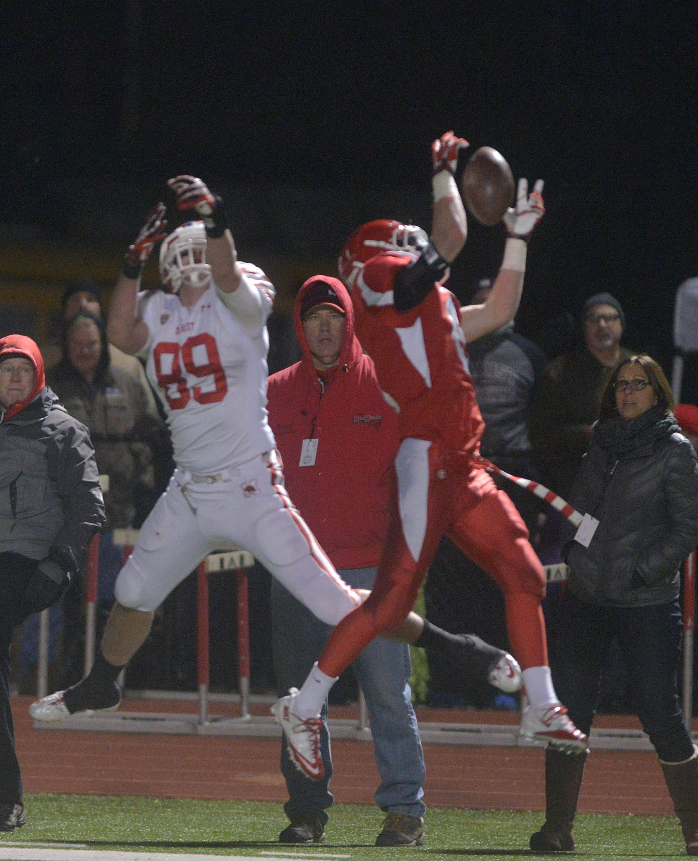 Nic Weishar of Marist,left, and Dillon Grooss go up for a pass during the Marist at Naperville Central football Class 8A semifinal Saturday.