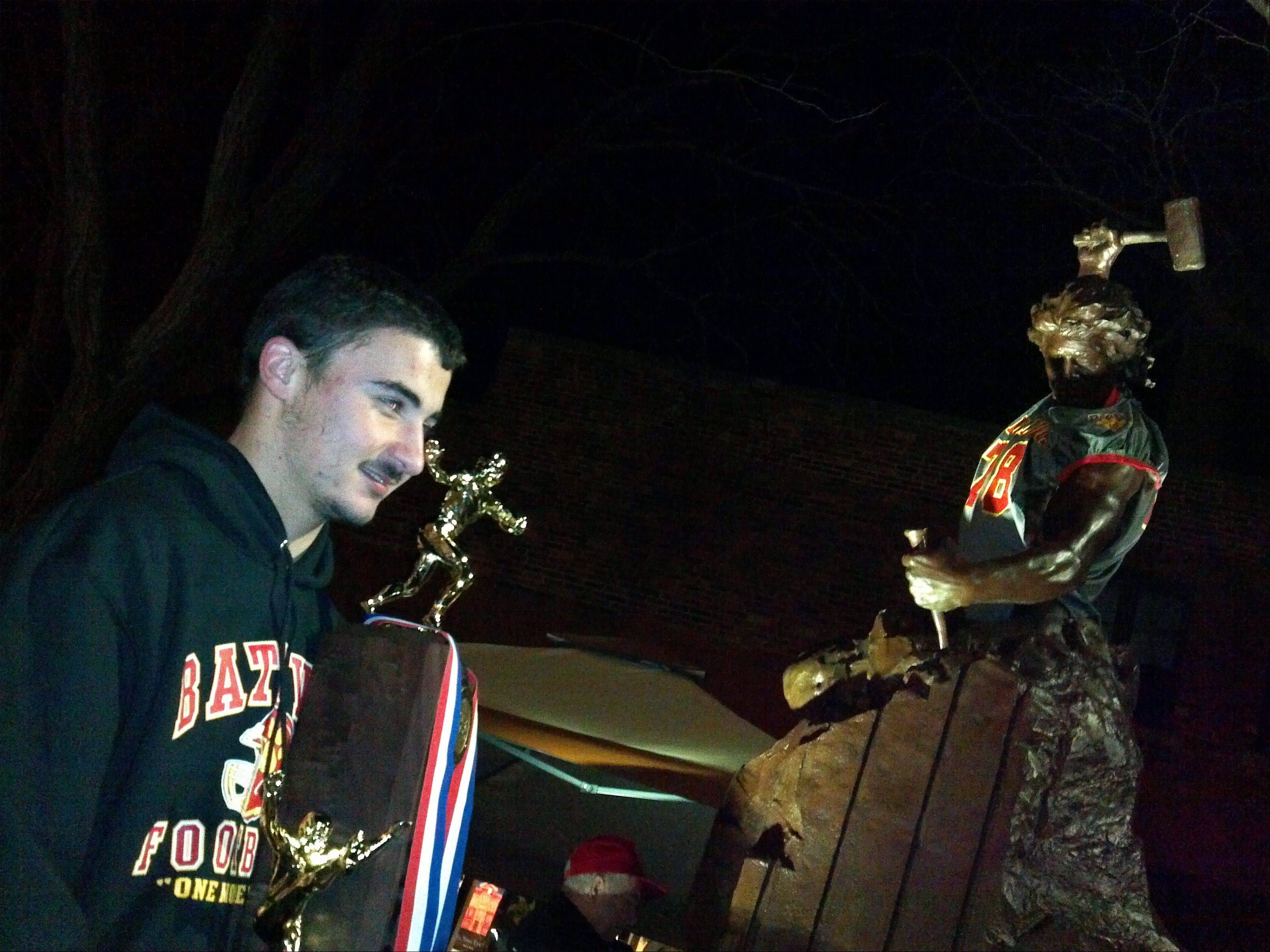 "David Lanciotti, linebacker for the Batavia High School football team, poses with the state championship trophy Saturday night in downtown Batavia with near the ""Self Made Man"" statue, also clad in a Bulldog jersey. ""This is such an amazing feeling. Once in a lifetime,"" said Lanciotti, a senior."