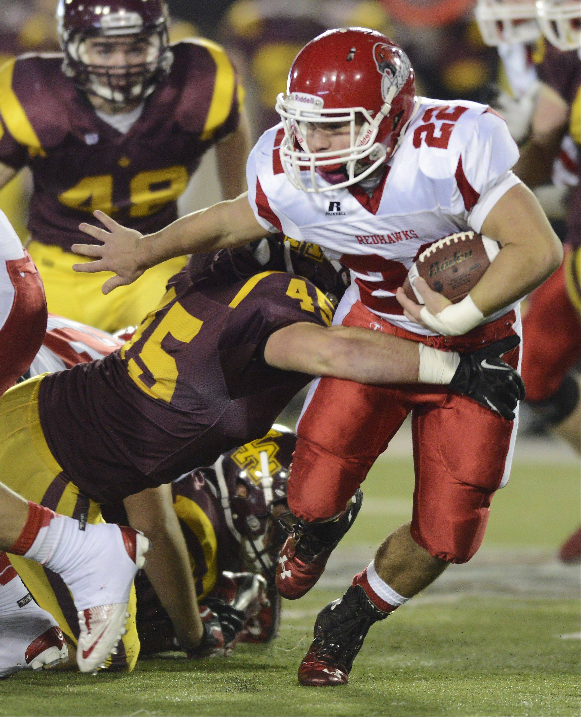 Naperville Central's Kevin Clifford tries to get past Loyola's Brian O'Brien during the Class 8A football final in DeKalb Saturday.