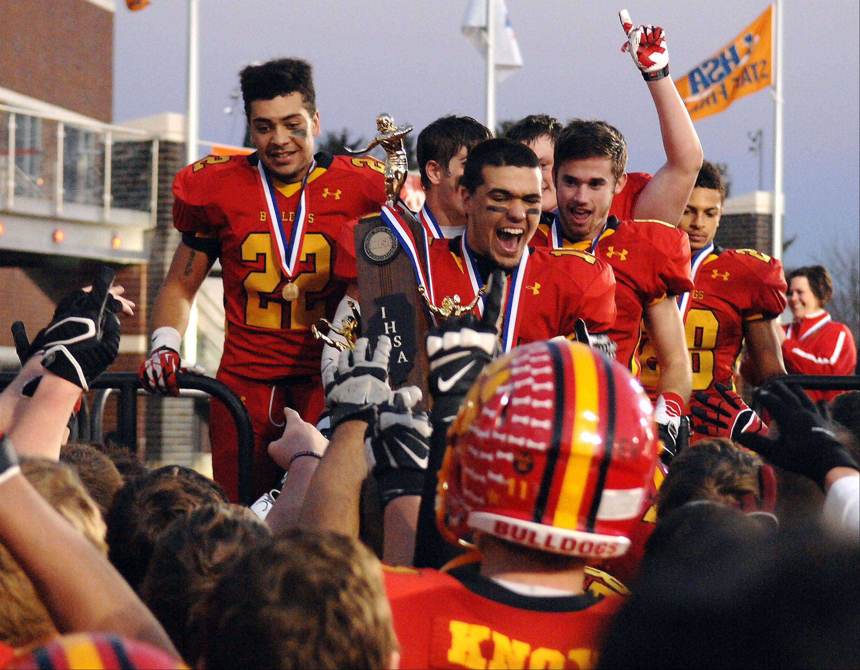 Batavia's Micah Coffey (15) brings the 6A championship trophy to his teammates after beating Richards Saturday in DeKalb.