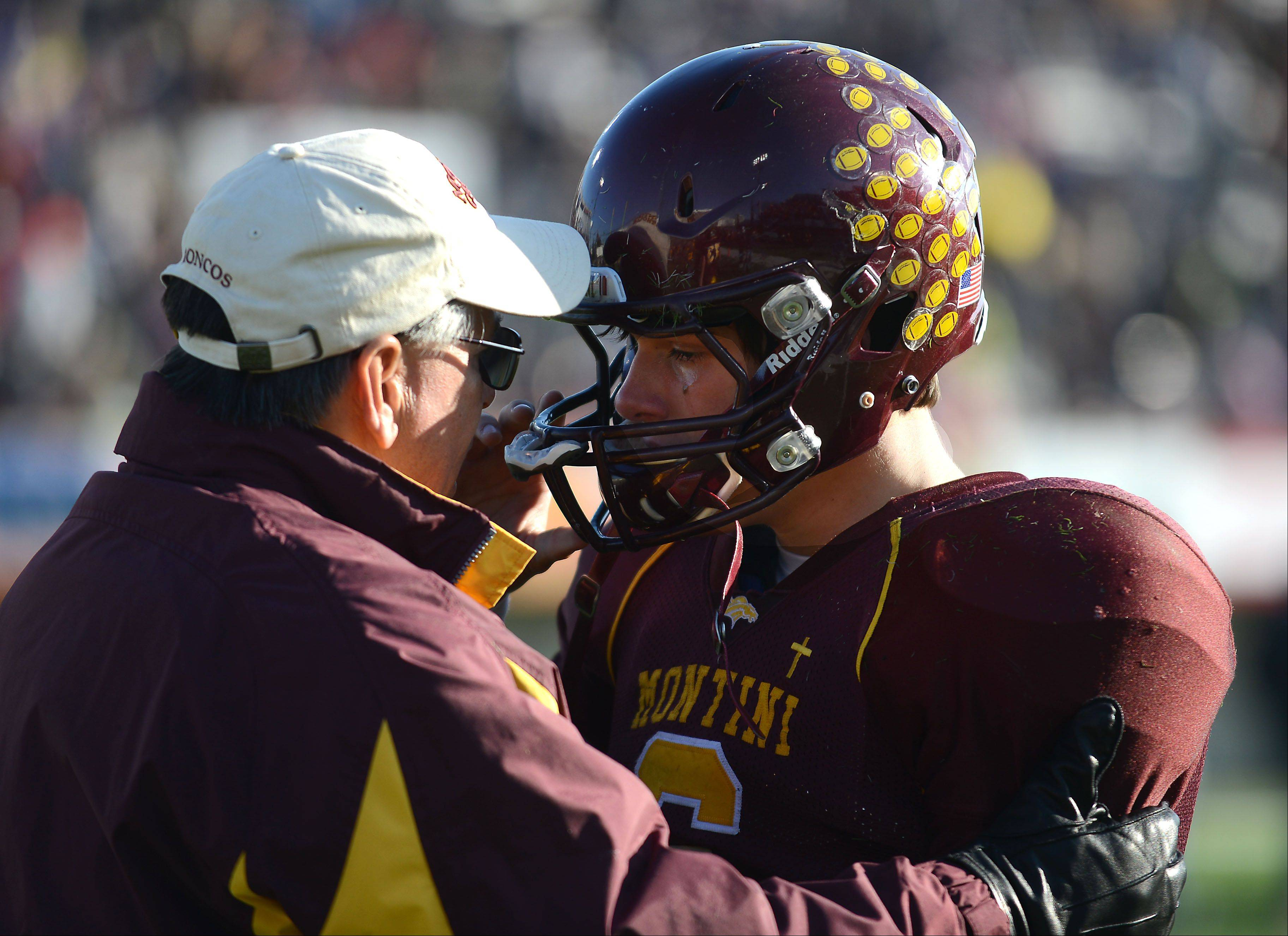 Montini coach Chris Andriano comforts quarterback Alex Willis (6) after Saturday's Class 5A championship loss to Sacred Heart-Griffin in DeKalb.