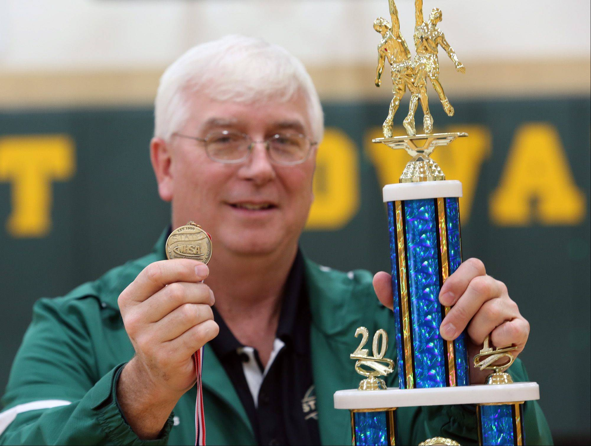 P.J. White, boys basketball coach and athletic director at St. Edward and an assistant football coach at Batavia, displays the state football championship medal from Saturday's Class 6A title game, and the championship trophy the St. Edward boys basketball team won Saturday night at Westminster Christian.
