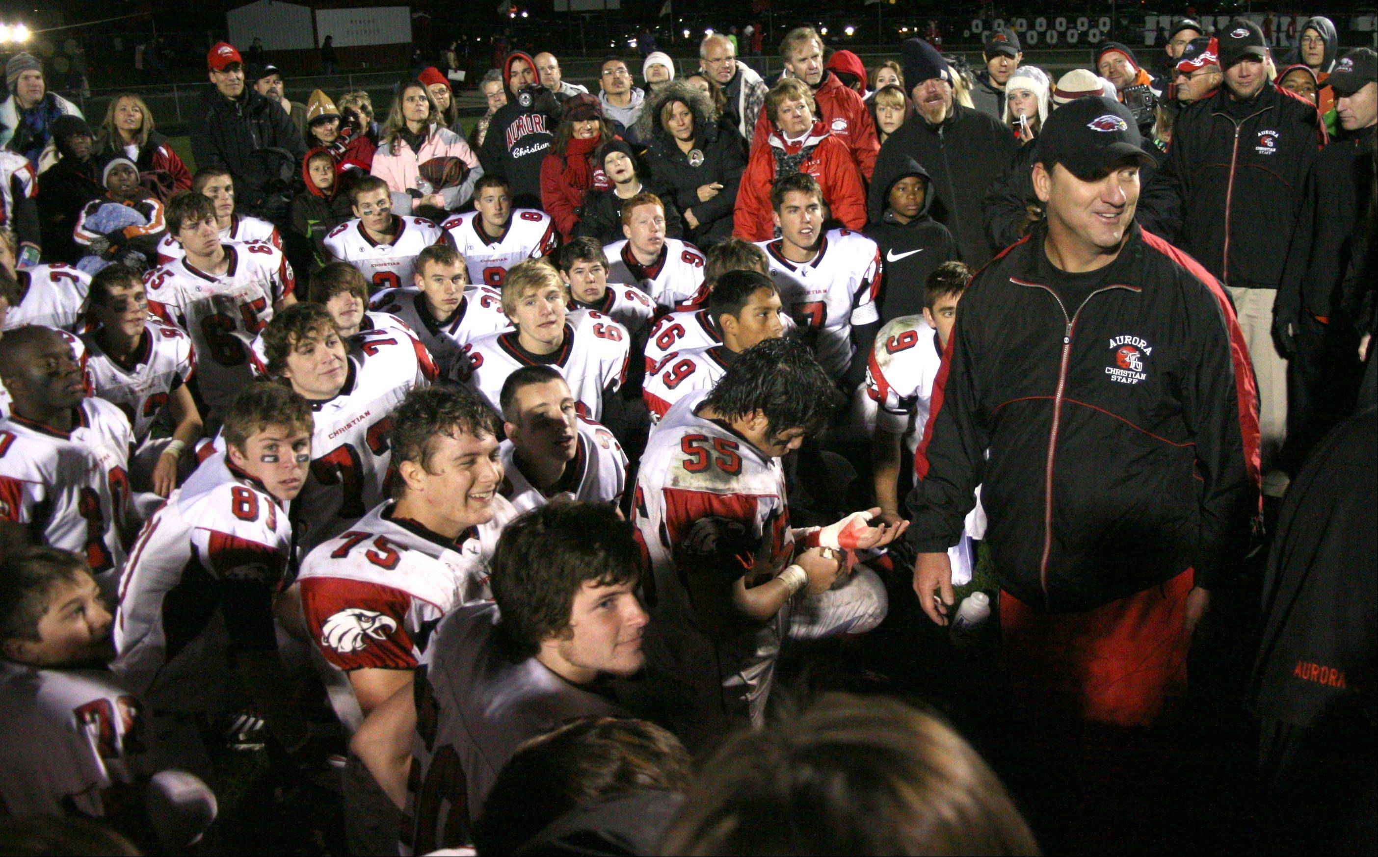Aurora Christian football coach Don Beebe addresses his team after a playoff victory at Oregon.