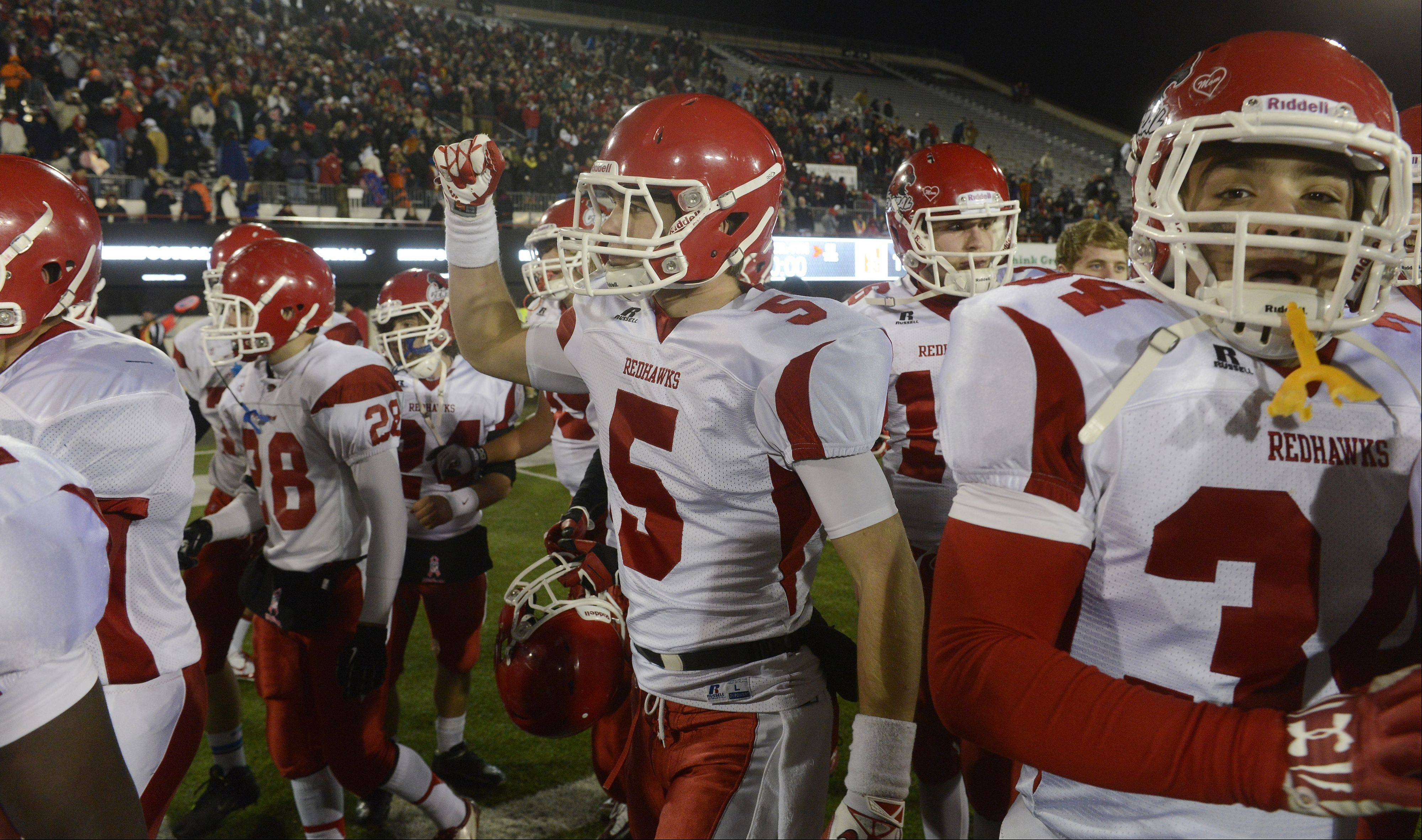 Naperville Central players celebrate and acknowledge the cheers from their fans after defeating Loyola Academy last month to win the Class 8A football title at Huskie Stadium in DeKalb on Nov. 30.