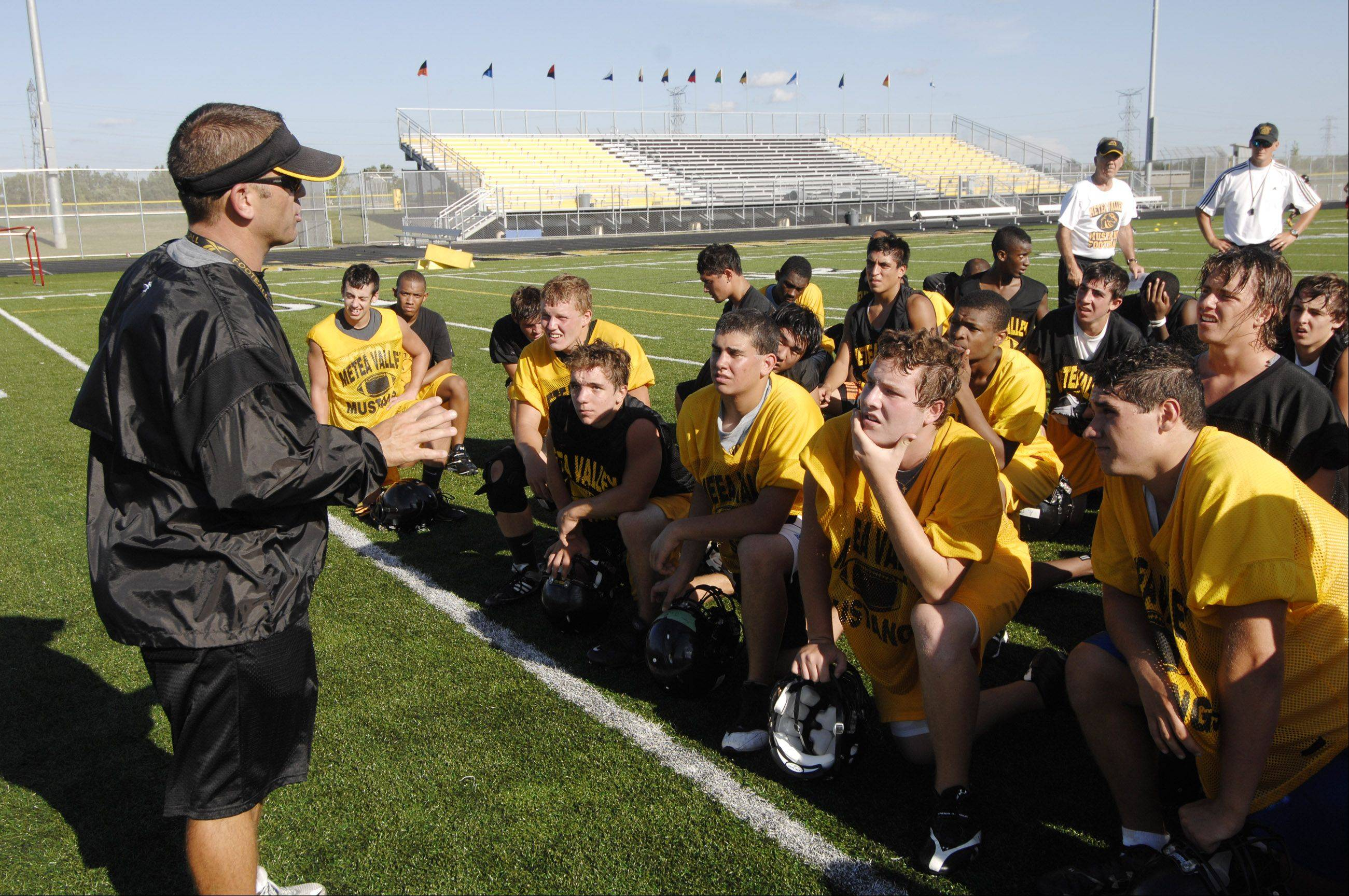 Head Coach Ted Monken addresses players on the first day of practice for Metea Valley High School's first varsity football squad.