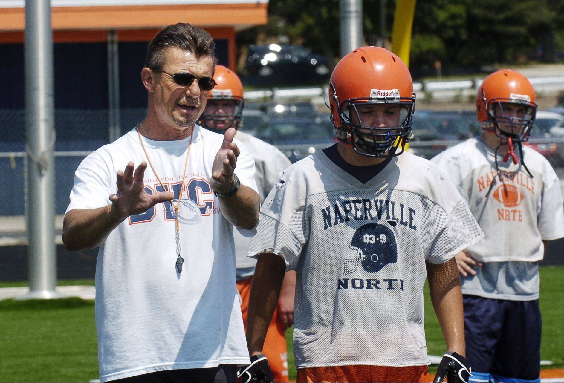 Head Coach Larry McKeon offers suggestions during practice. The Naperville North Huskies football team takes to its field resplendent with a new Field Turf artificial playing surface for the first time this year on Wednesday, August 12.