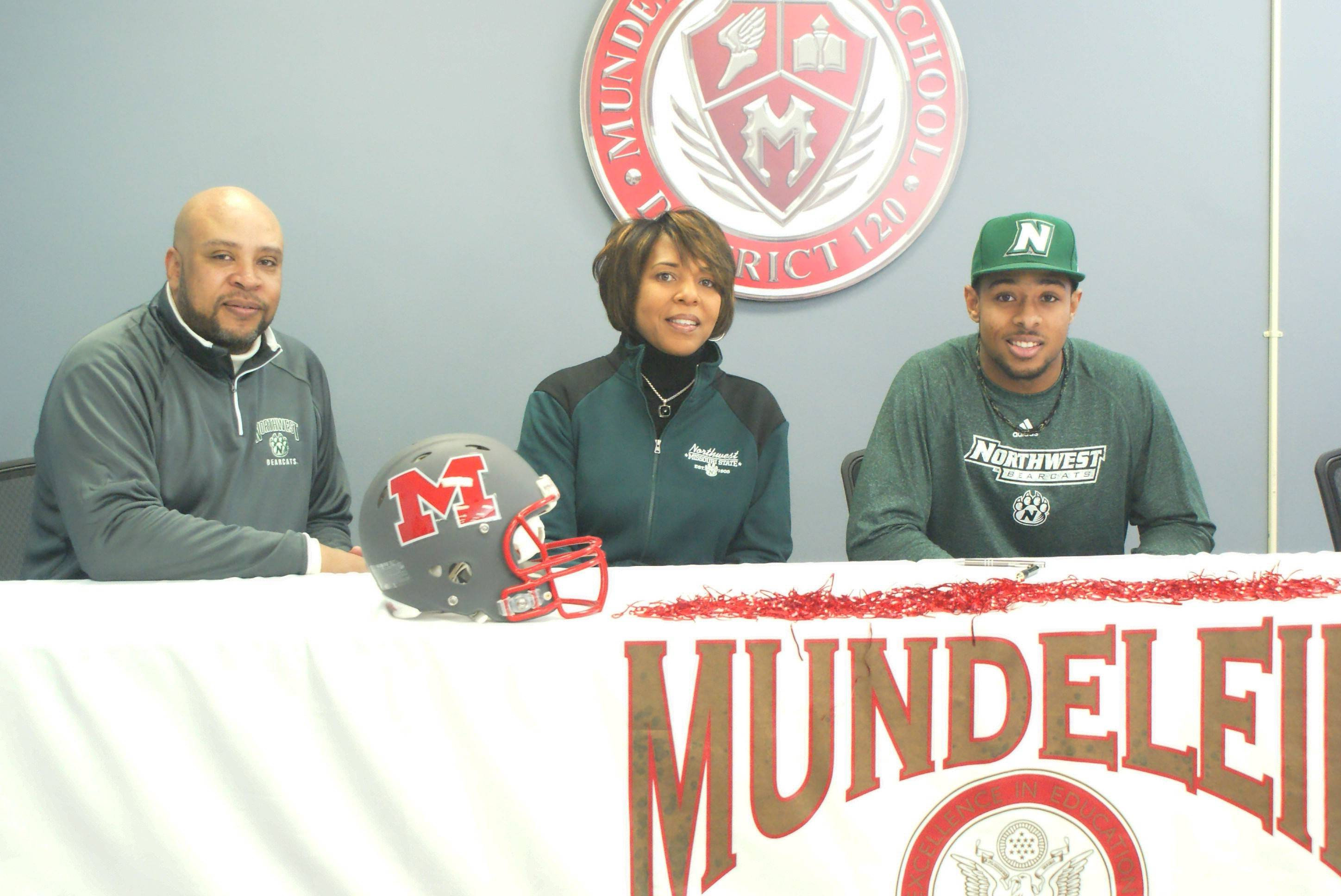 Mundelein senior Emanuel Jones poses with his parents, Vince and Dietra, after signing to play football with Northwest Missouri State University.