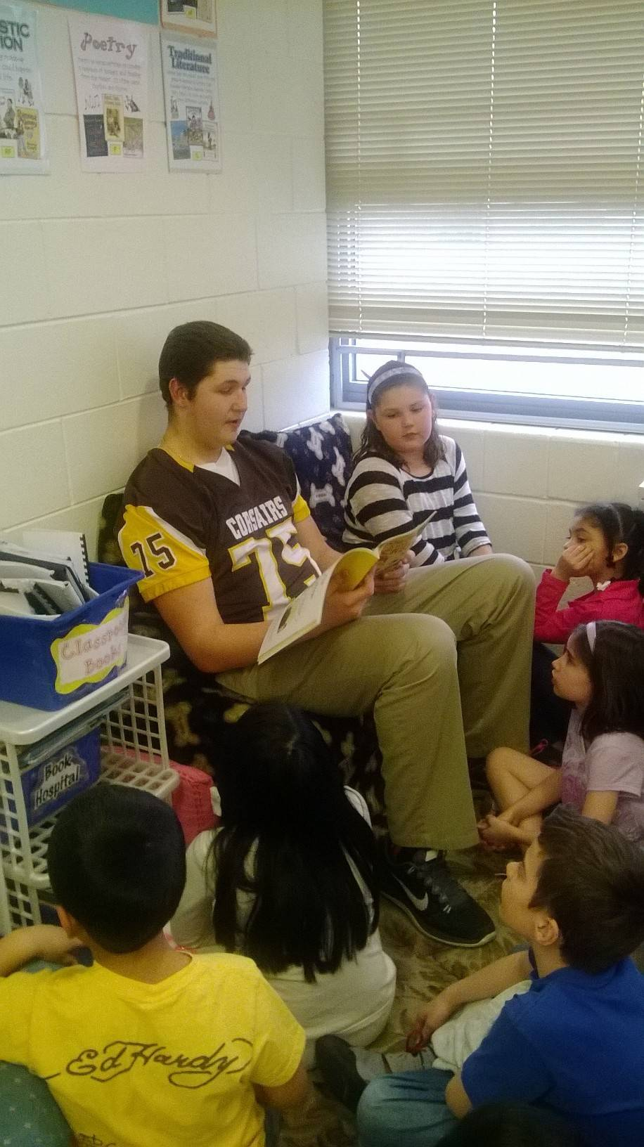 Carmel sophomore football player Sean Foster reads to second-graders at Freemont Elementary School in Mundelein. Foster's sister, Rylan, is sitting next to him.