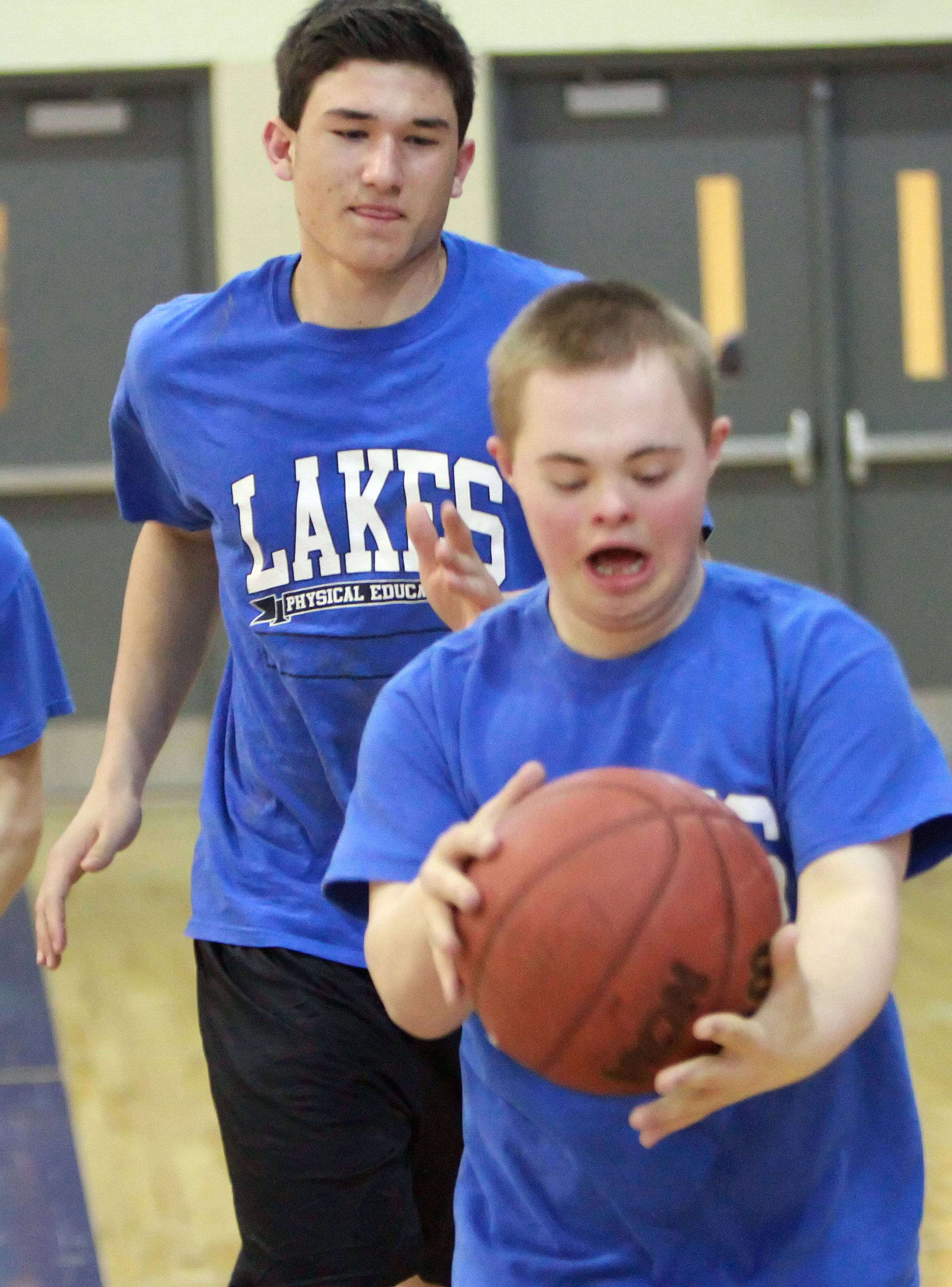 Lakes outfielder Ethan Sage, left, works with 15-year-old Matthew Kramer, who has Downs Syndrome, during PE class Thursday. Sage helped to start a Big Buddies program at Lakes High School that works with special needs male students to help them fit in at school.
