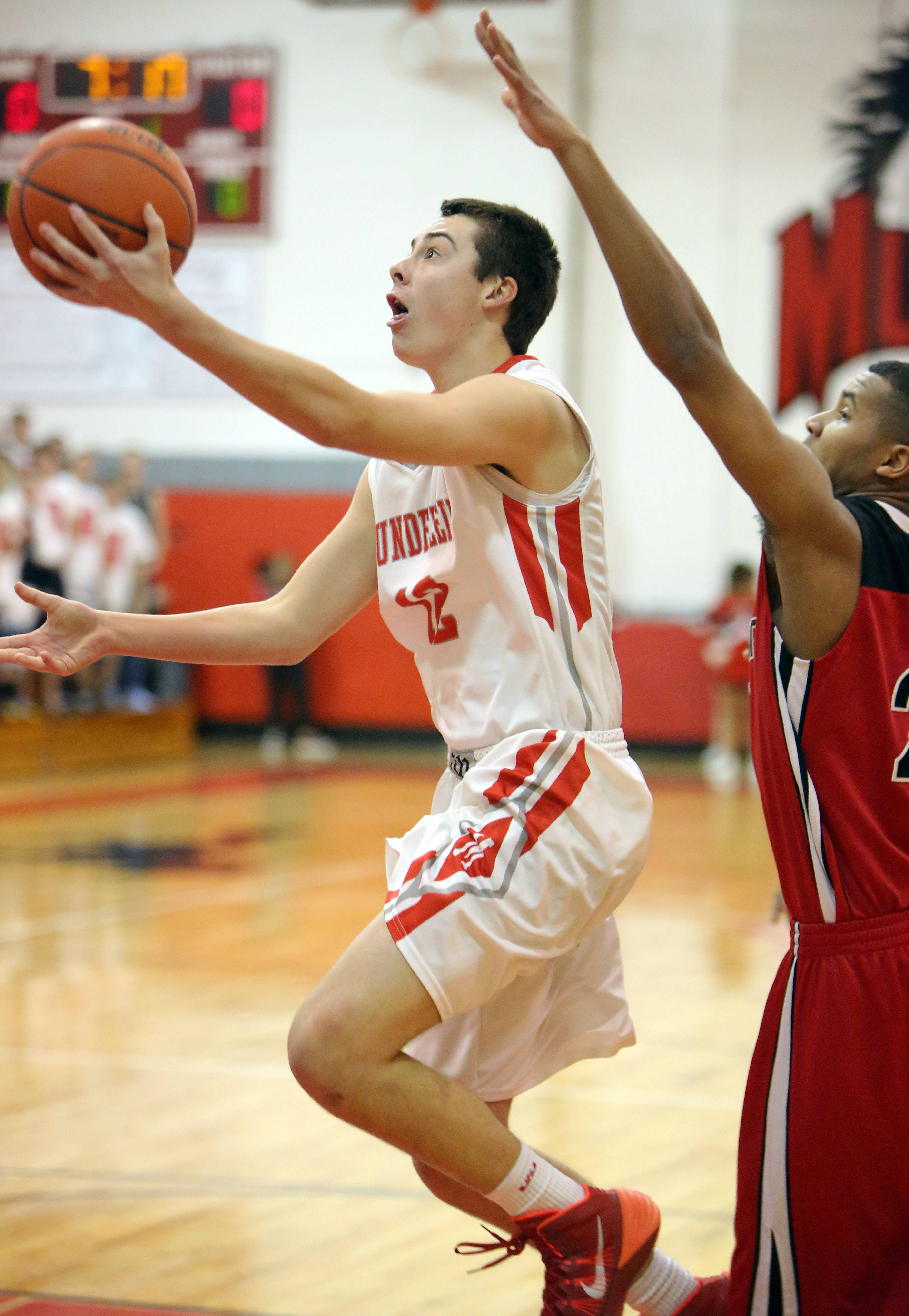 Mundelein's Derek Parola, left, drives to the hoop past Grant's Steve Dunning.