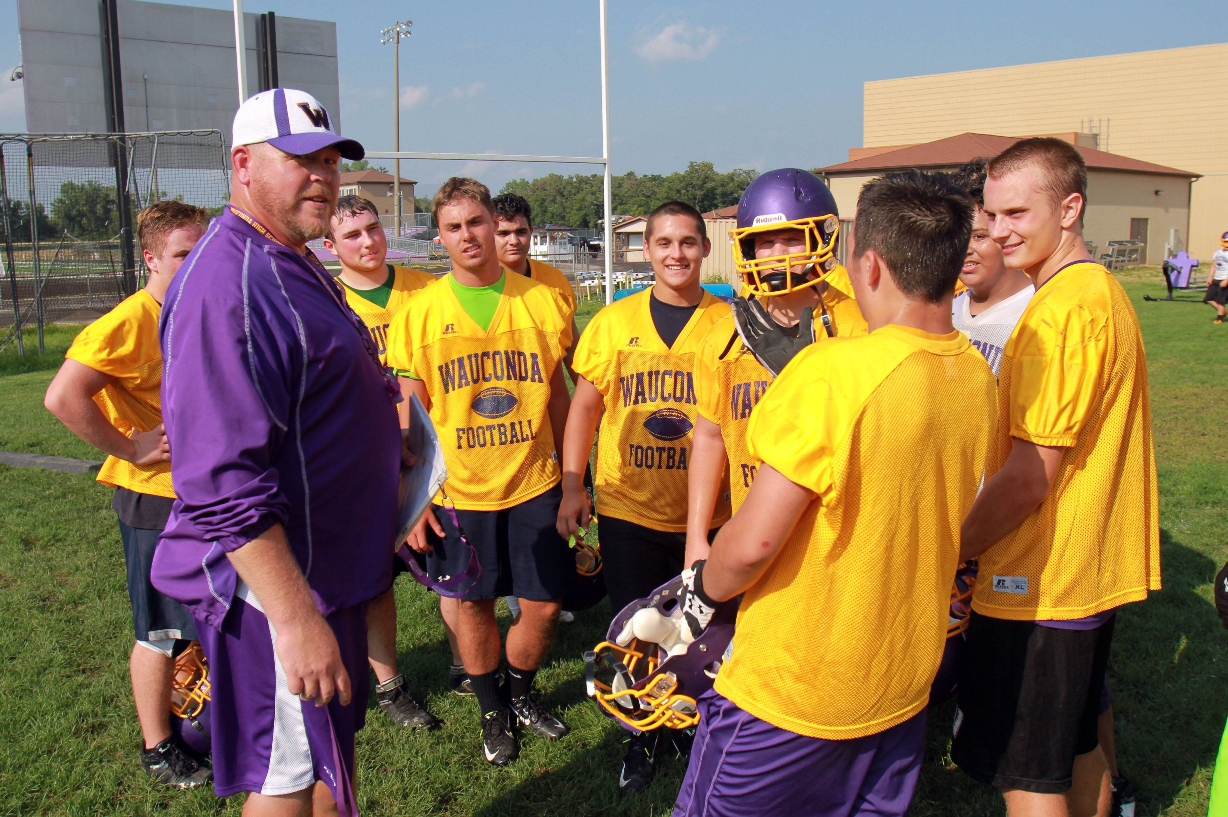 Defensive coordinator Sean Rudolph talks to his players during football practice Monday at Wauconda High School.